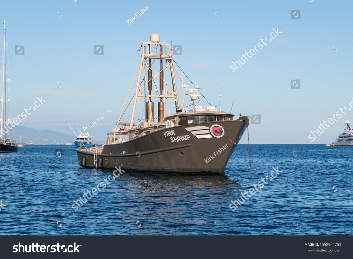 Villefranche Sur Mer, France - September 28 2019: A black shrimp boat trawls for shrimp in a bay along the Southern coast of France near the French Riviera.