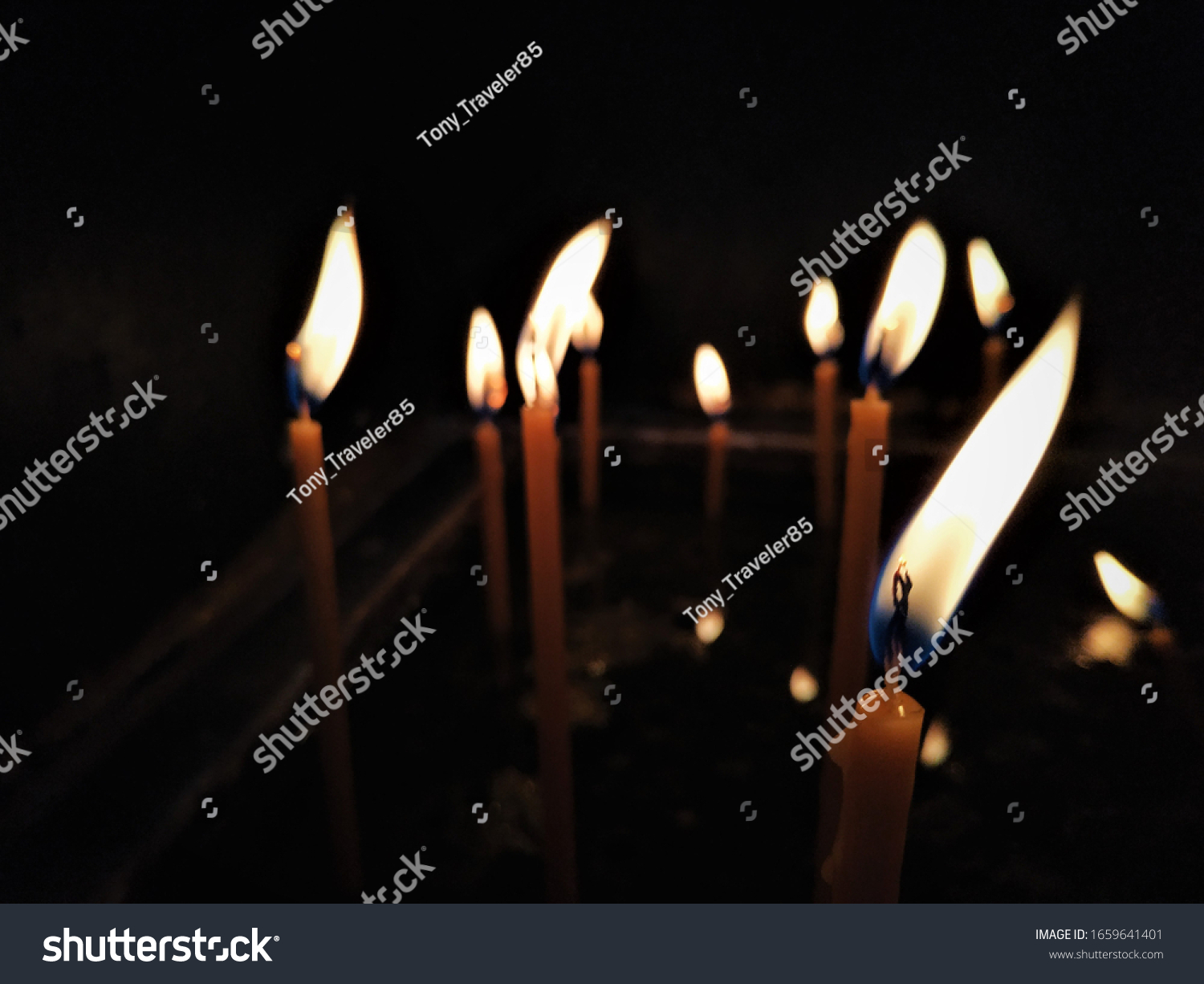 Candles on a dark background, candles flame at night closeup, cozy interior.