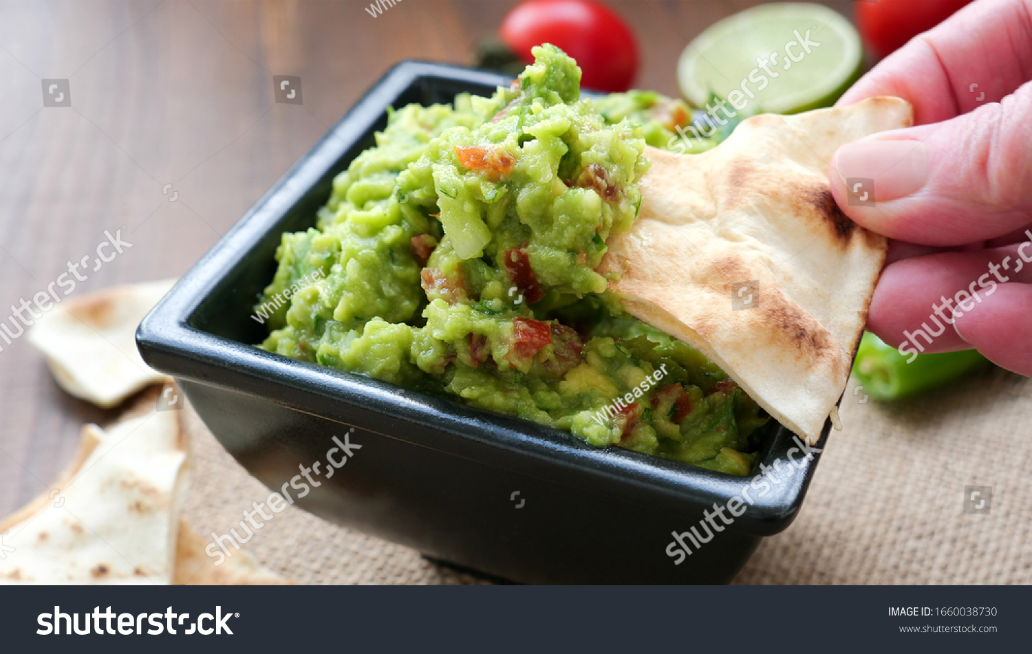 Hand dipping wheat tortilla chips into a bowl of freshly made guacamole dip