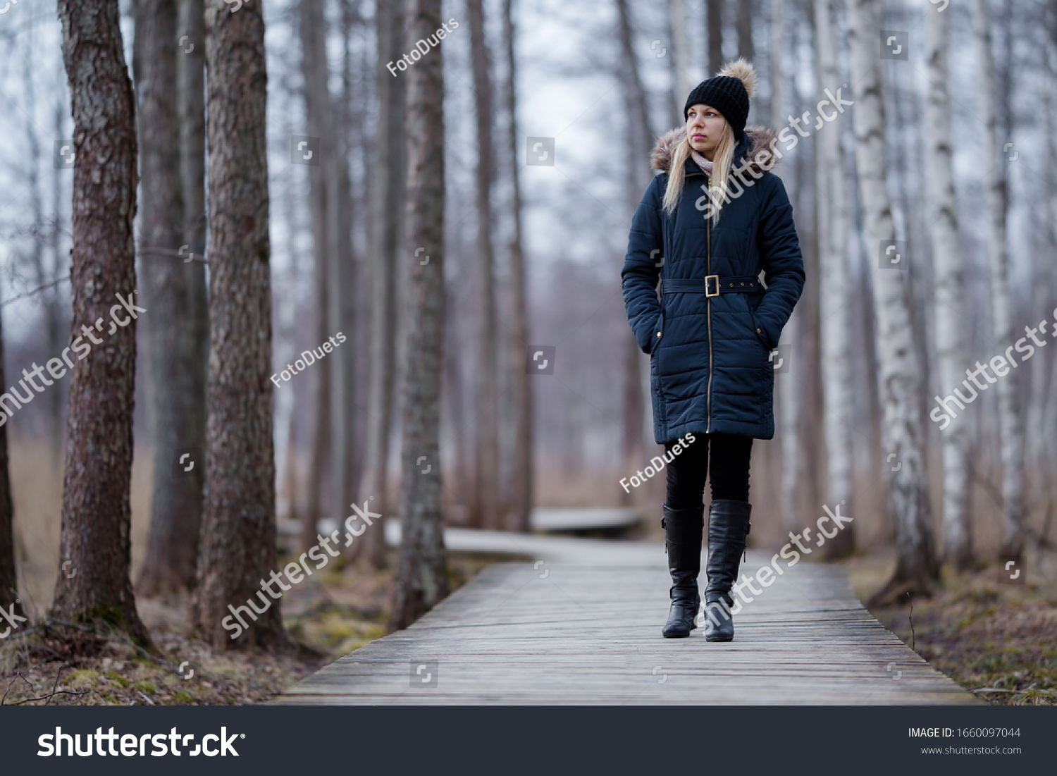 Young woman in dark warm clothes slowly walking on wooden trail at natural park. Cold overcast day. Spending time alone in nature. Peaceful atmosphere. Front view.