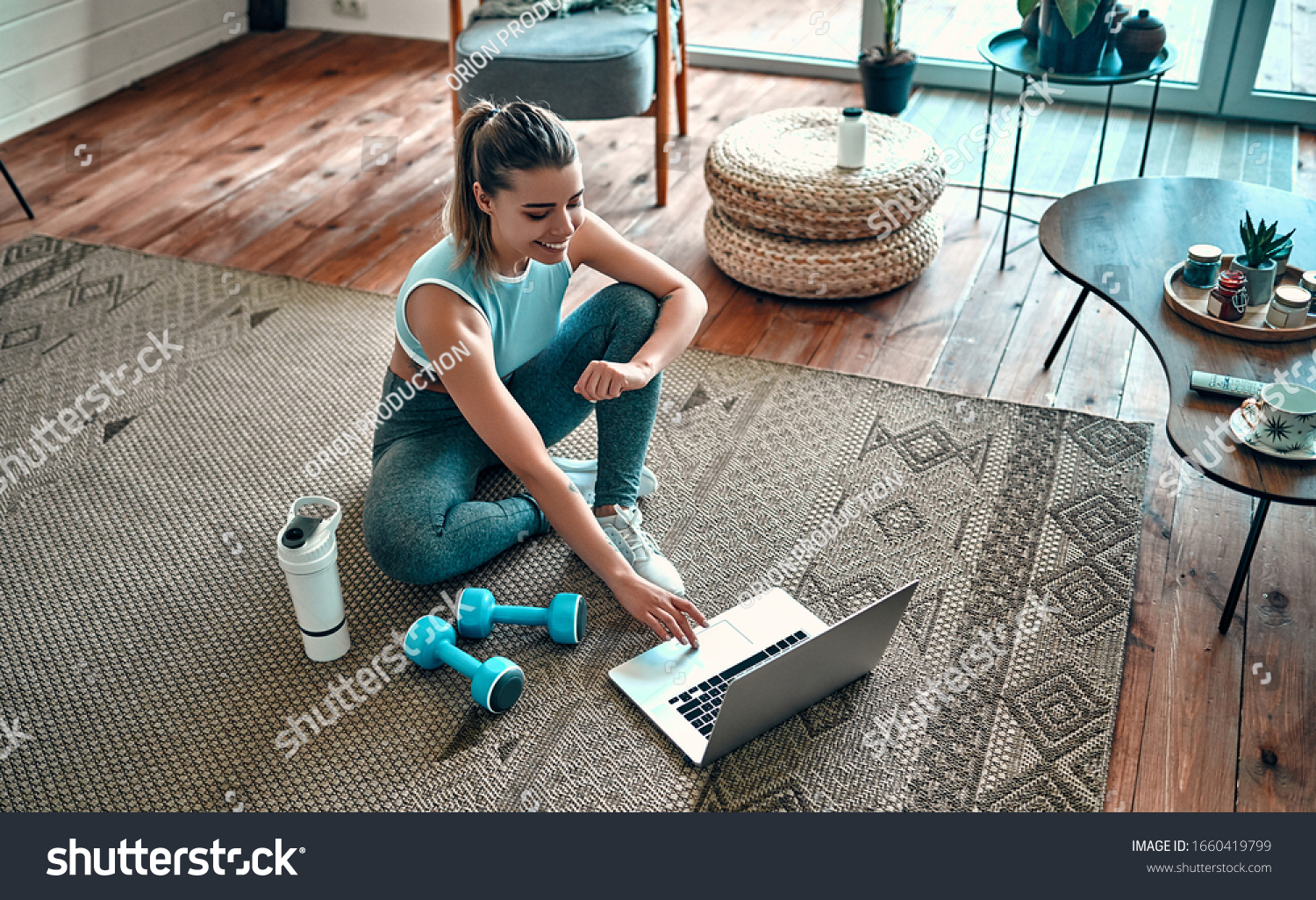 A sporty woman in sportswear is sitting on the floor with dumbbells and a protein shake or a bottle of water and is using a laptop at home in the living room. Sport and recreation concept. #1660419799