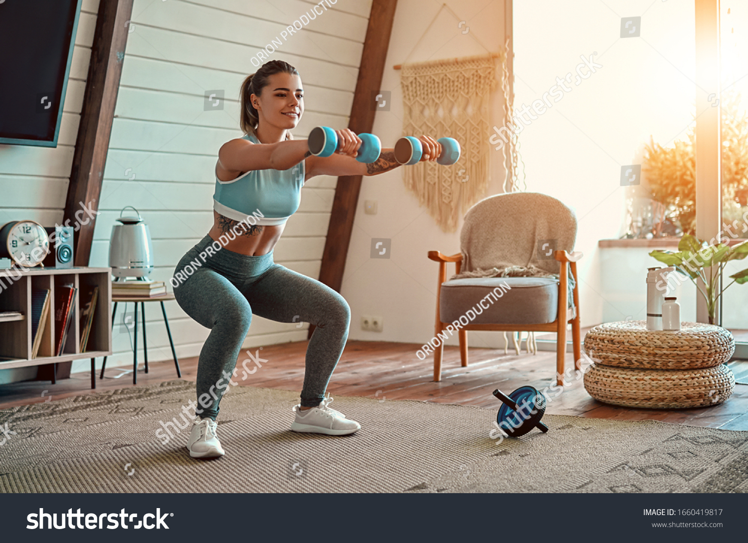 Beautiful young athletic girl in leggings and top crouches with dumbbells at home. Sport, healthy lifestyle. #1660419817