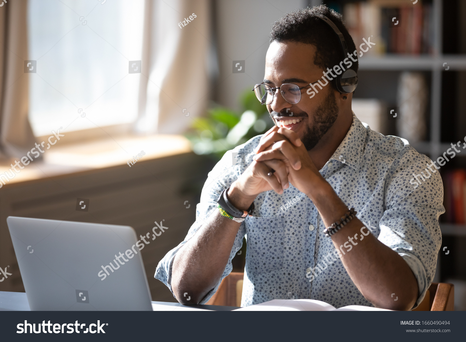 Happy millennial african american man in glasses wearing headphones, enjoying watching educational webinar on laptop. Smiling young mixed race businessman holding video call with clients partners. #1660490494