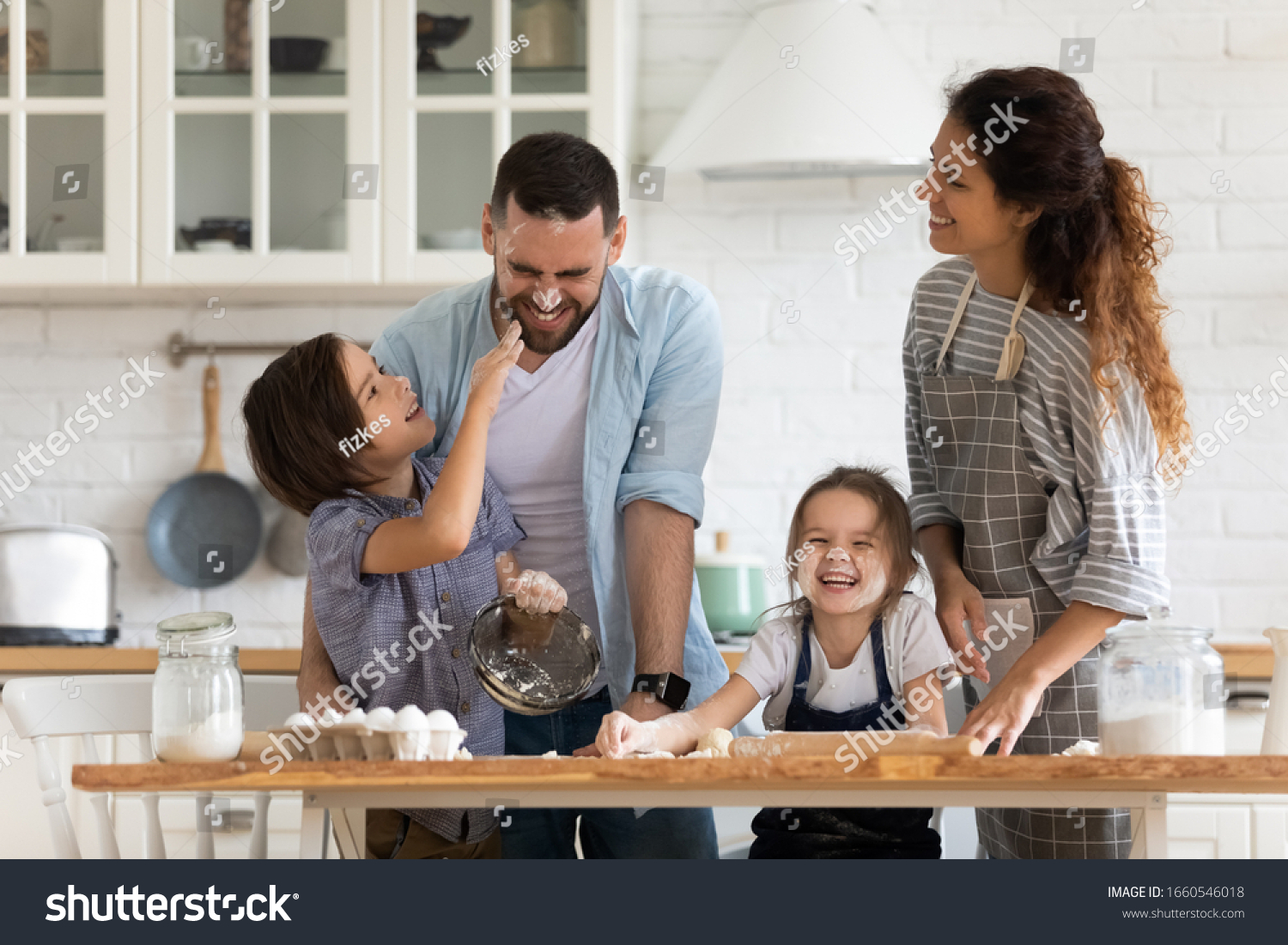 Overjoyed young family with little preschooler kids have fun cooking baking pastry or pie at home together, happy smiling parents enjoy weekend play with small children doing bakery cooking in kitchen #1660546018