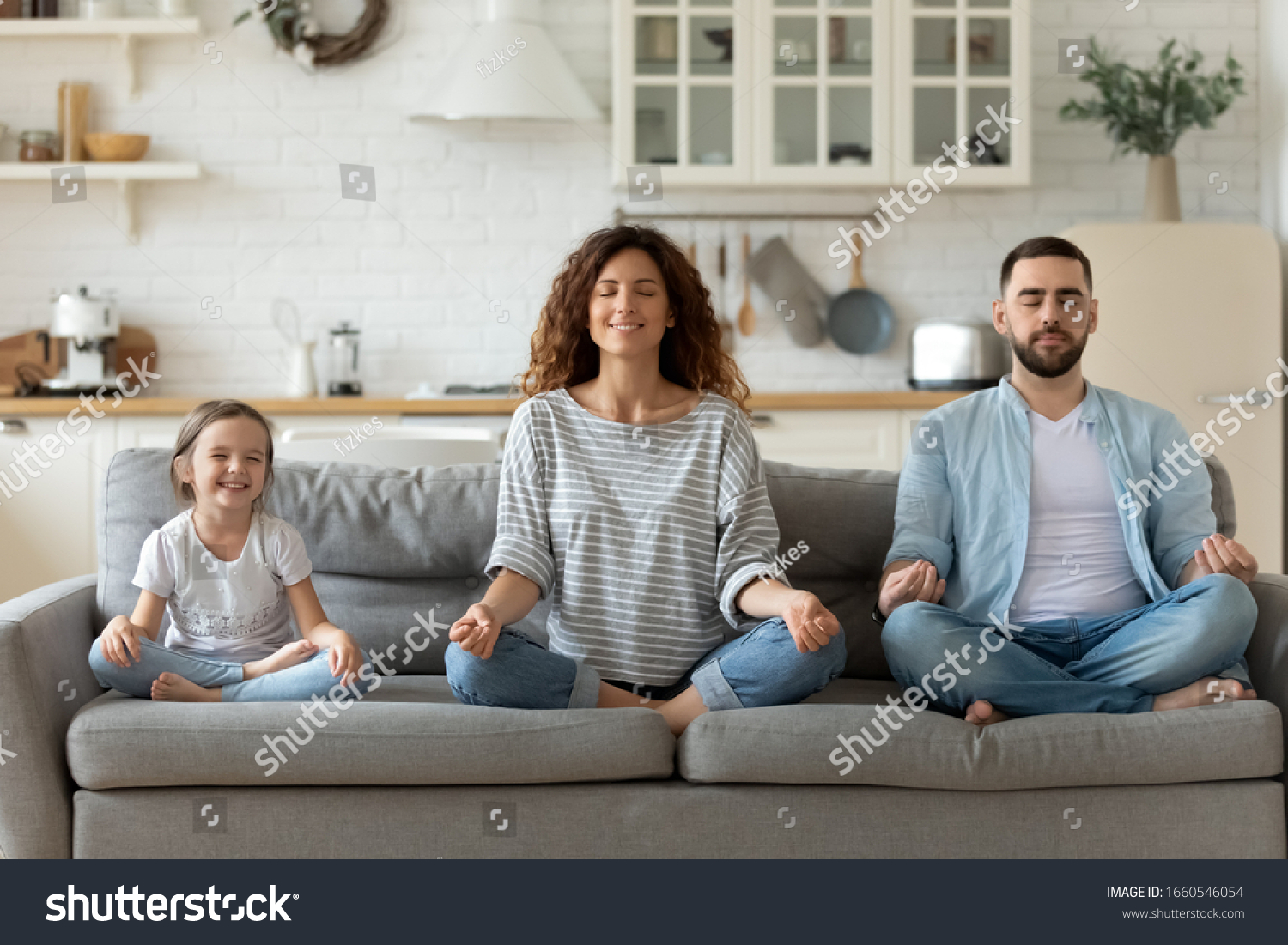 Calm young family with little daughter sit on couch practice yoga together, happy parents with small preschooler girl child rest on sofa meditate relieve negative emotions on weekend at home #1660546054