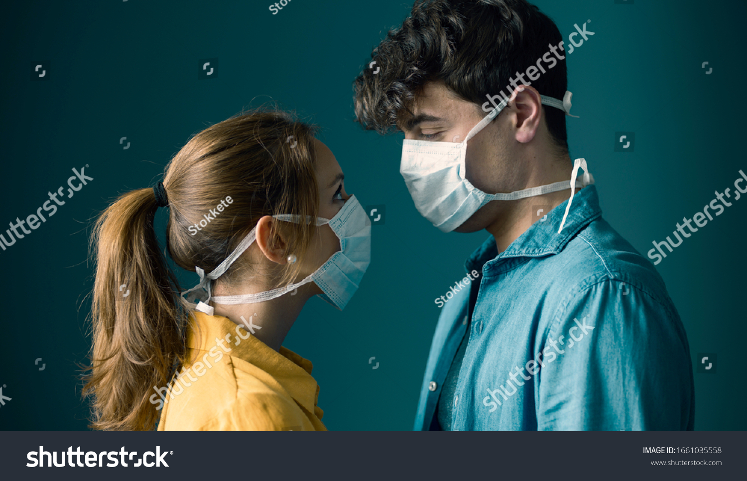 Young romantic loving couple wearing a protective face mask and staring at each other's eyes, pandemic and feelings concept #1661035558