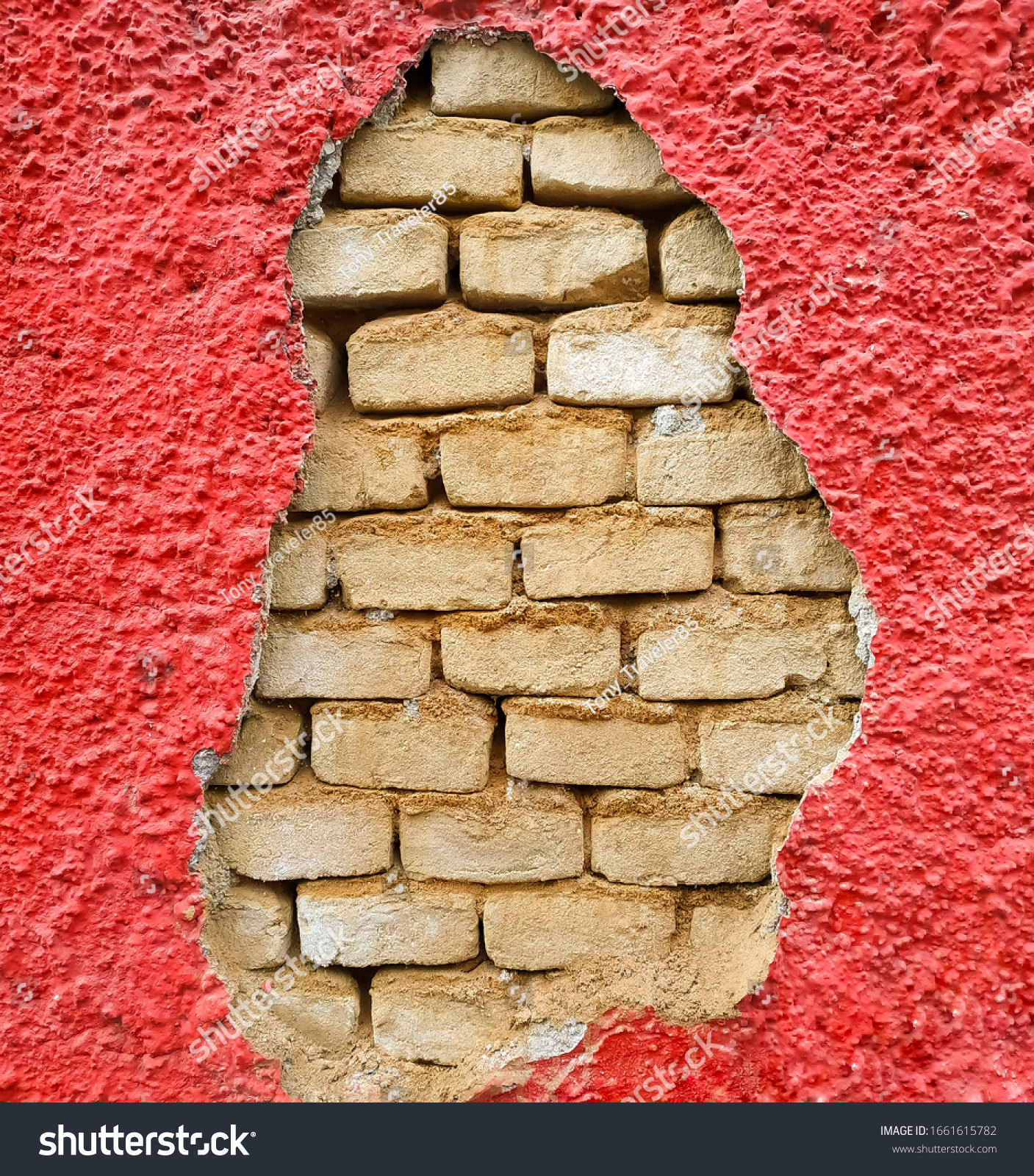 Exposed brickwork on a red wall.