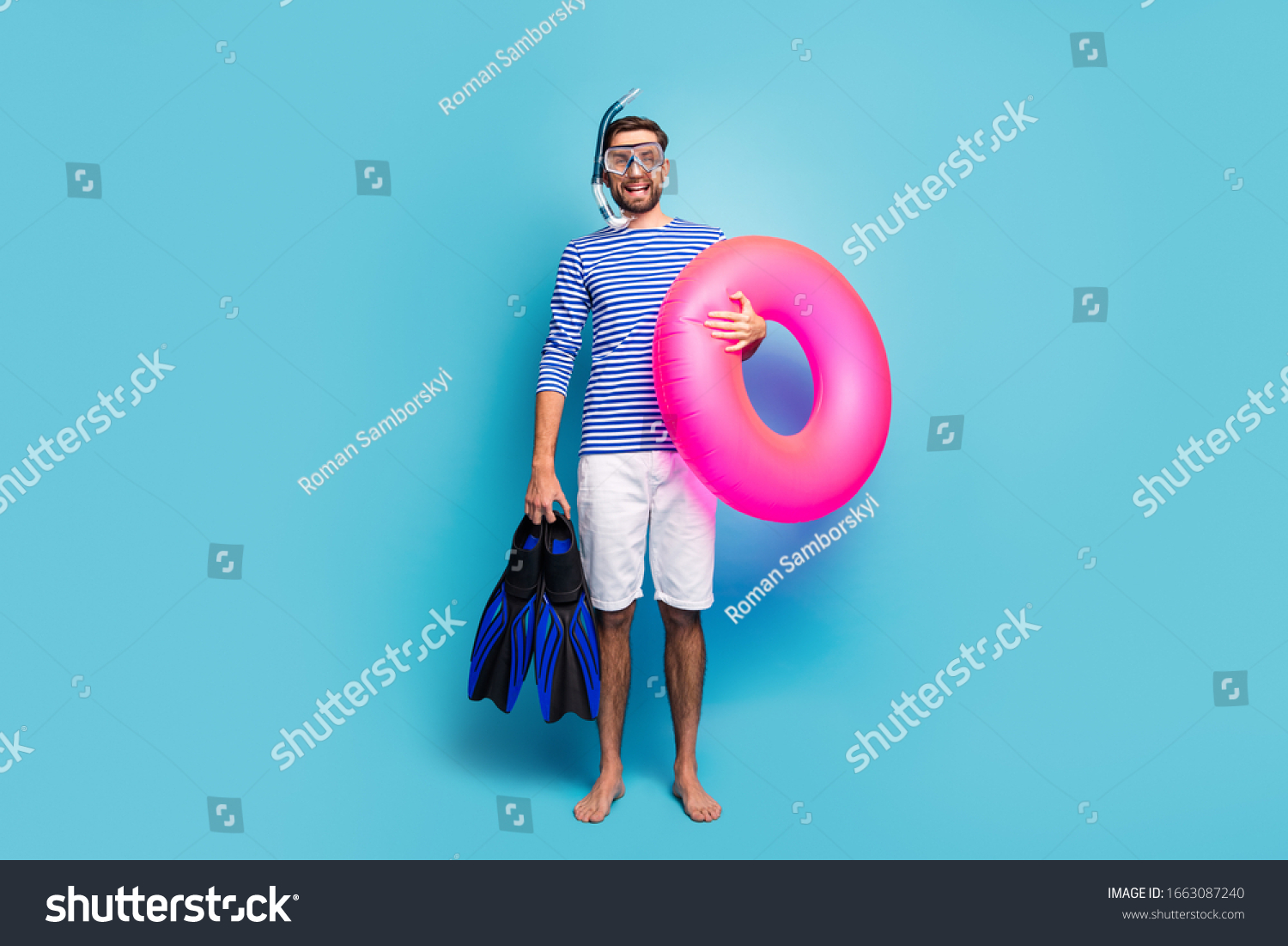 Full body photo of funny excited guy tourist swimmer hold underwater mask breathing tube flippers pink lifebuoy wear striped sailor shirt shorts isolated blue color background #1663087240