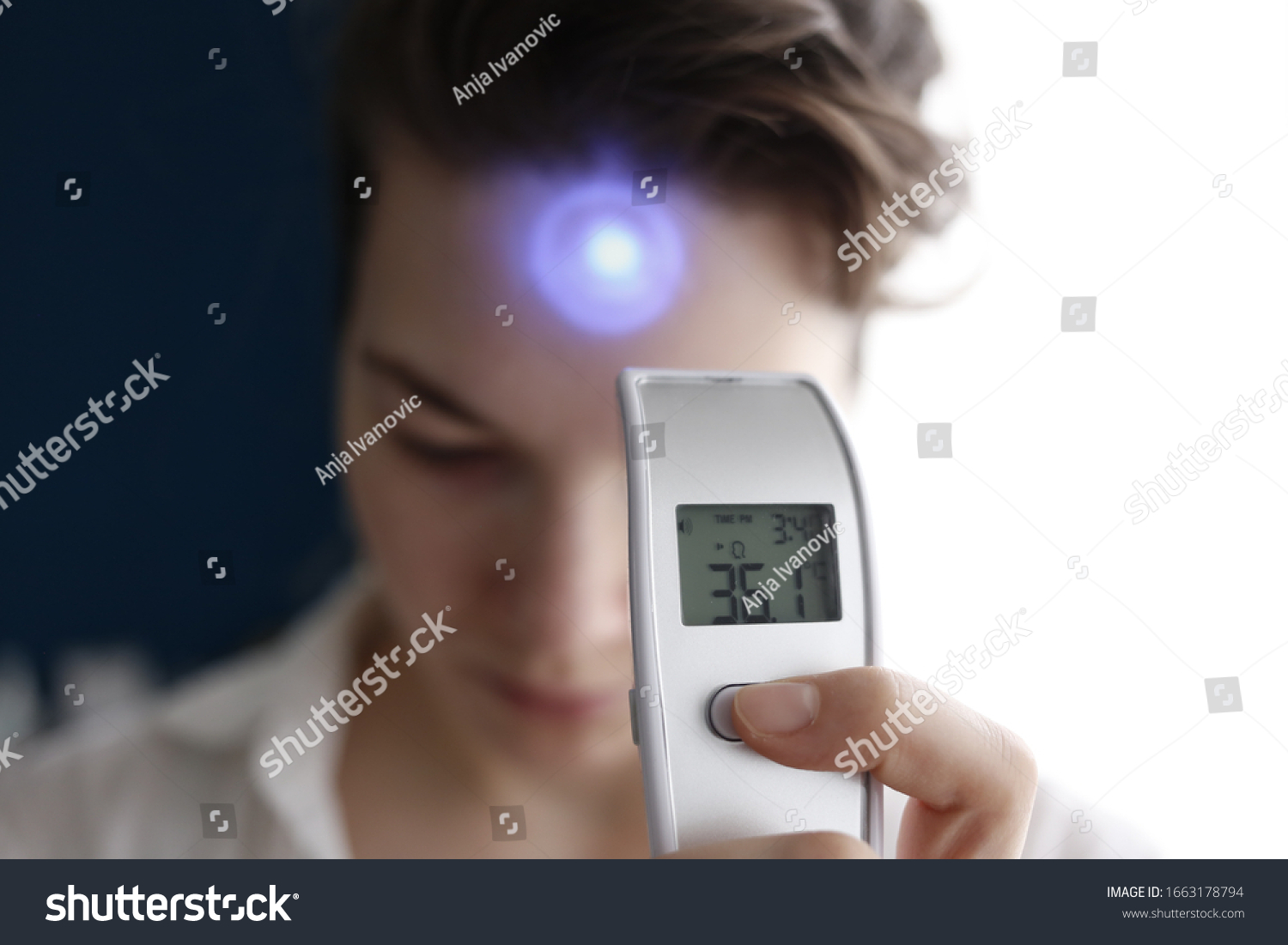 A female person being measured body temperature with a contactless thermometer #1663178794