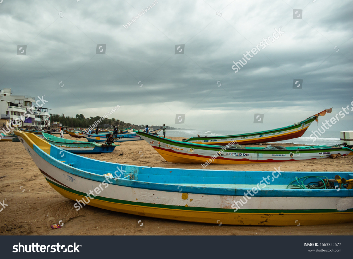 Mamallapuram, Tamil Nadu, India - August 2018: Fishing boats idle on the Mahabalipuram beach on a cloudy day.