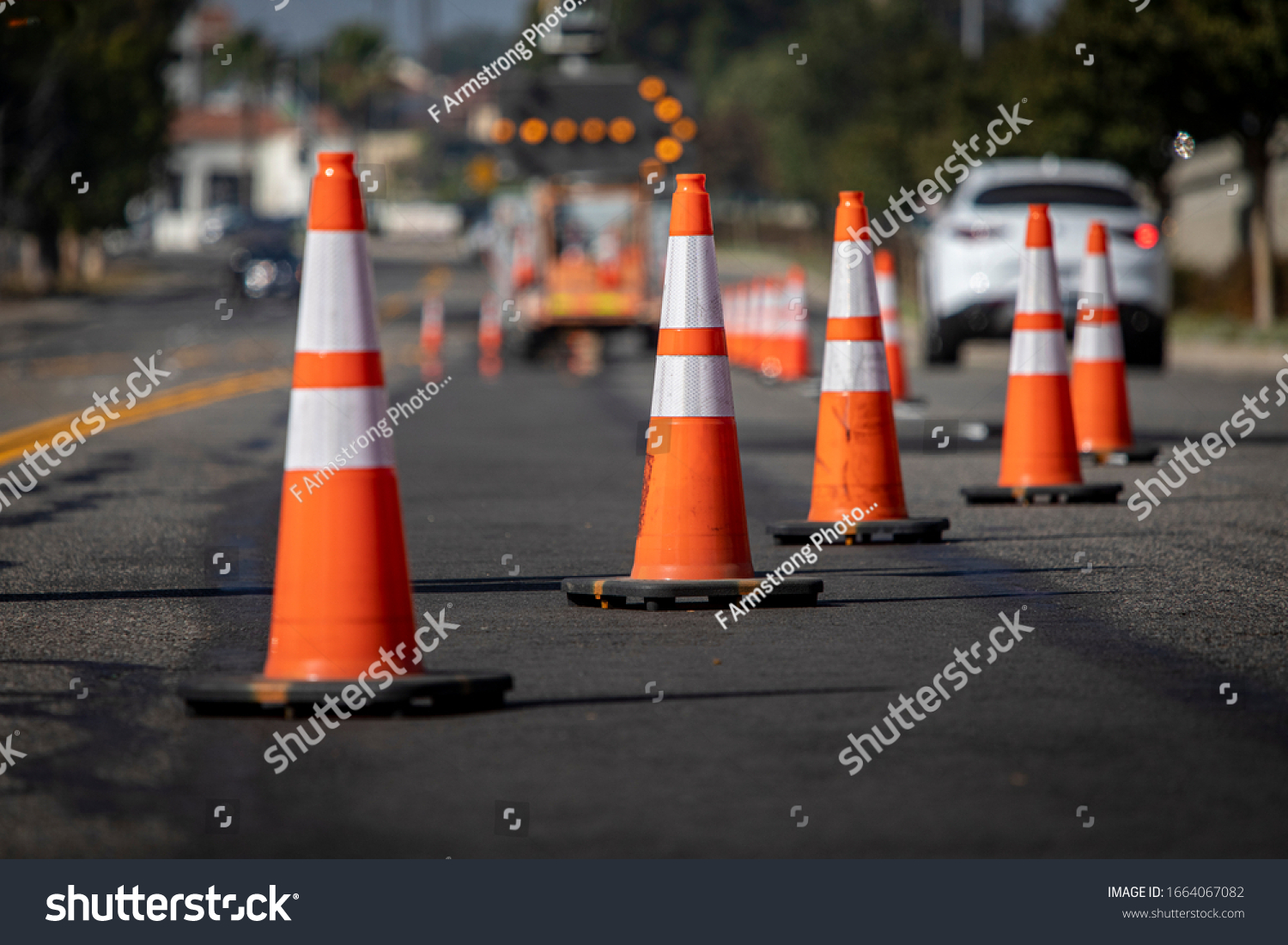 Traffic cones on road with electronic arrow pointing to the right to divert traffic and white car in distance #1664067082