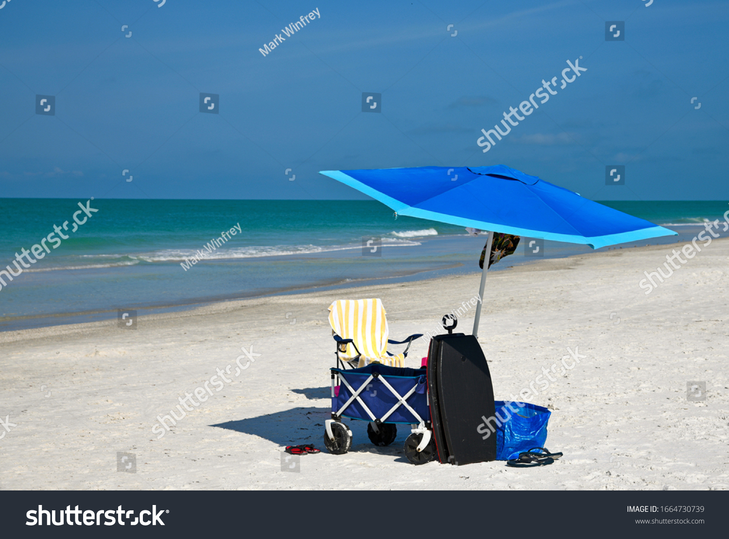 A Blue Beach Umbrella and Chair with Miscellaneous Beach Items to Enjoy a Day at the Beach