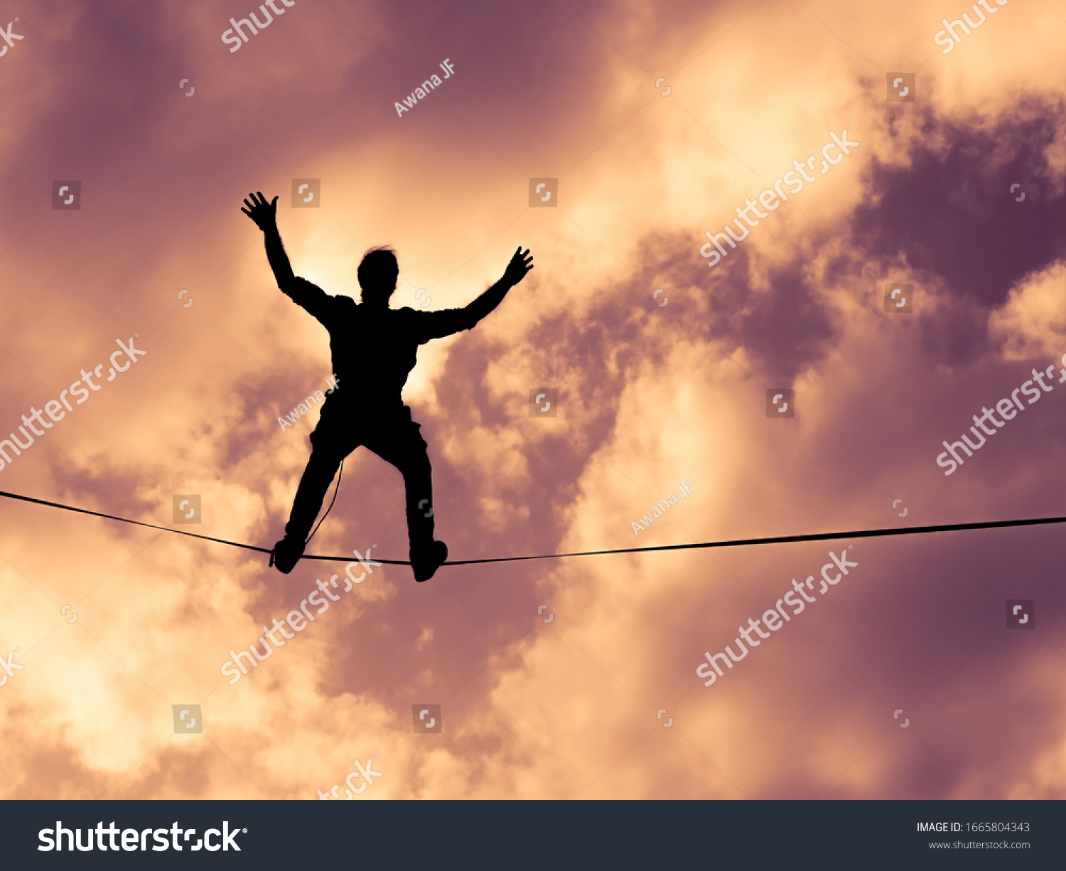 Natural image of a silhouette of tightrope acrobat walking on a hanging wire with a natural colorful and cloudy sky background