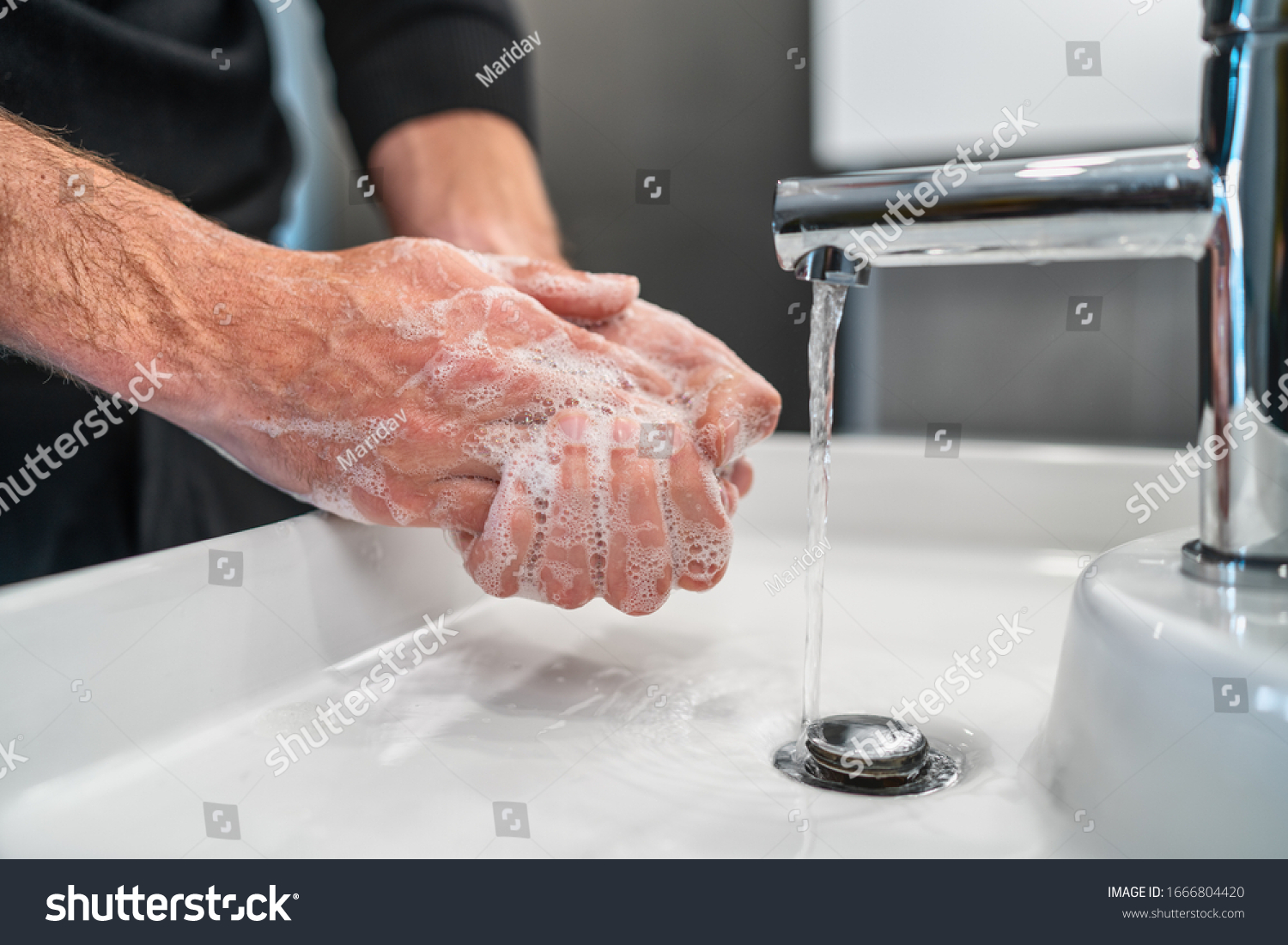 Corona virus travel prevention man showing hand hygiene washing hands with soap in hot water for coronavirus germs spreading protection. #1666804420