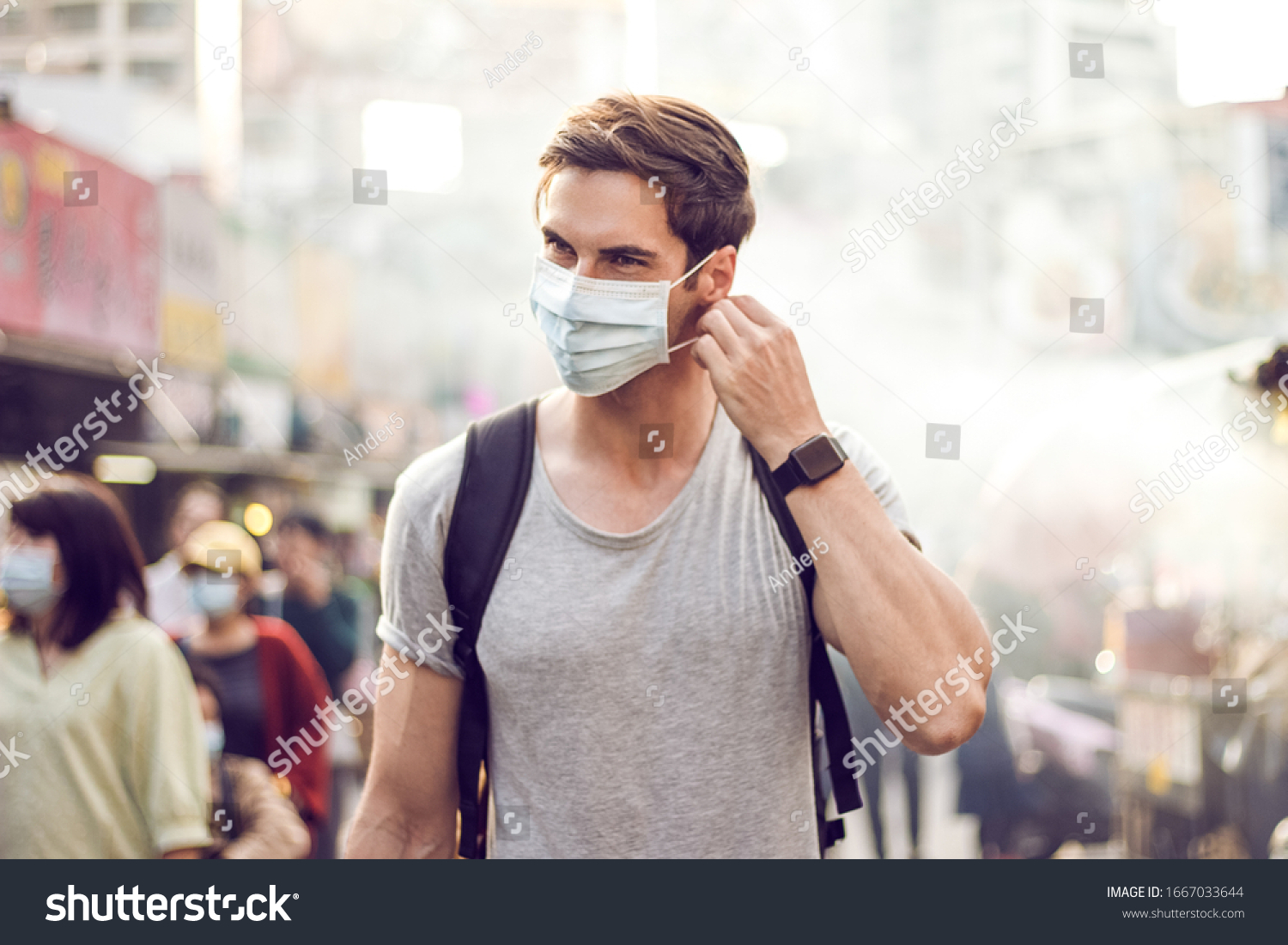 Young handsome man walking around night market in Taipei with backpack and wearing a face pollution mask to protect himself from the coronavirus. #1667033644