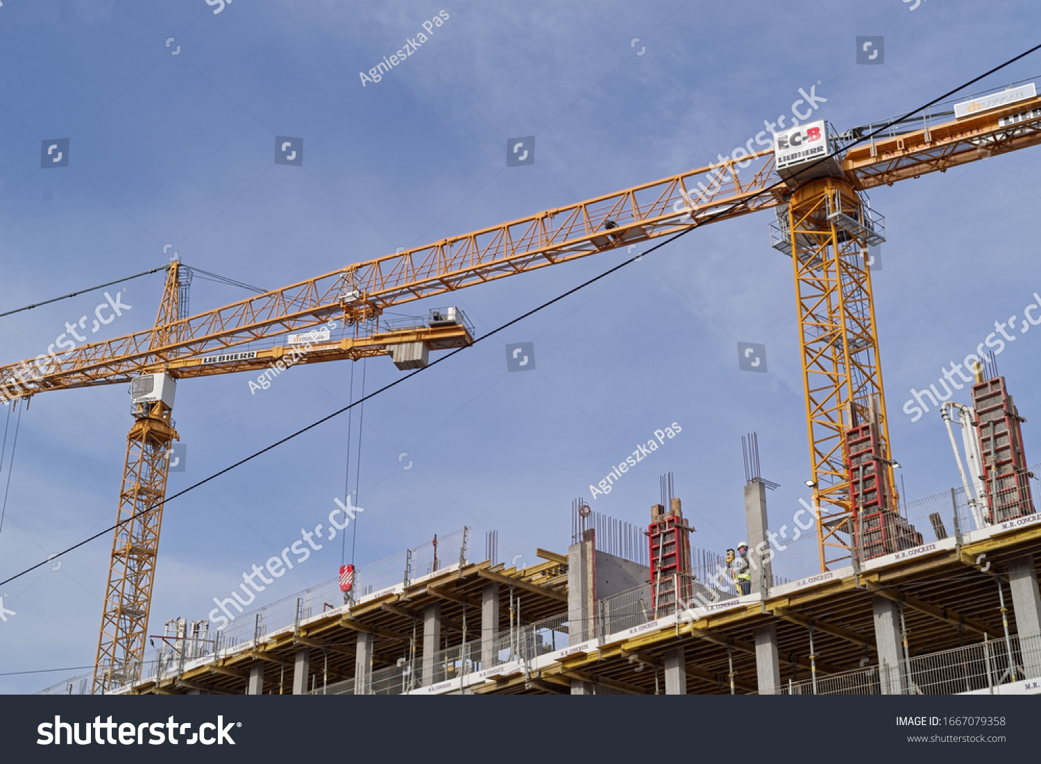 DUBLIN, IRELAND - MARCH 5, 2020: Building construction site with tower cranes against blue sky. View from below.