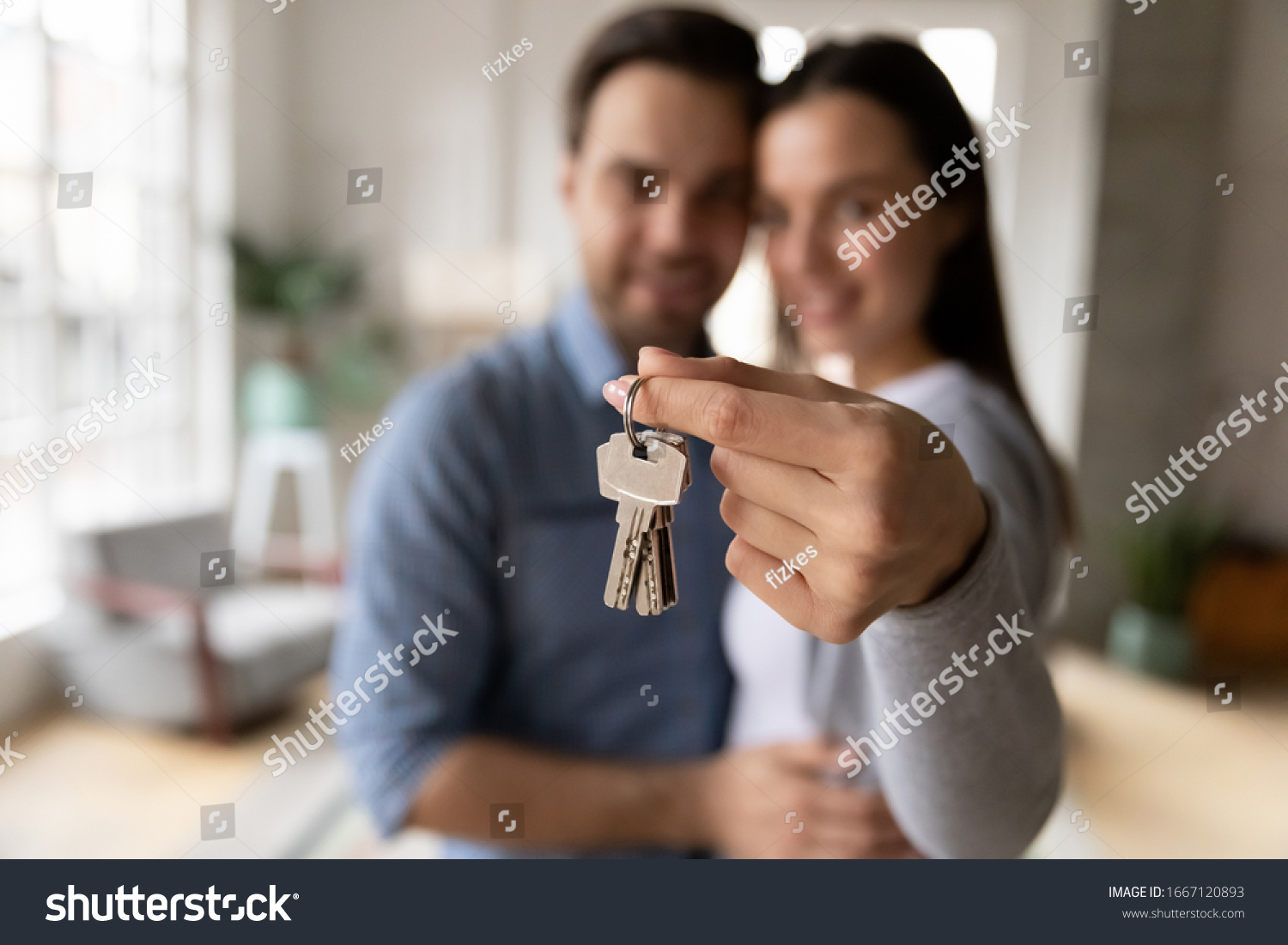 Focus on keys, held by excited young spouses homeowners. Happy married family couple celebrating moving in new house home , demonstrating keys, standing in apartment, real estate mortgage concept. #1667120893