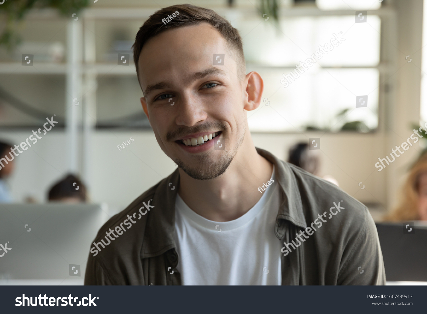 Headshot portrait of smiling millennial male employee talk on video call or web conference in coworking office, profile picture of happy Caucasian young man worker posing in shared workplace #1667439913