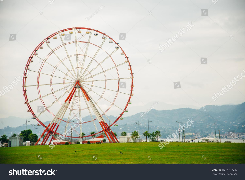 Ferris wheel on embankment of Batumi at sunny day.... #1667516596