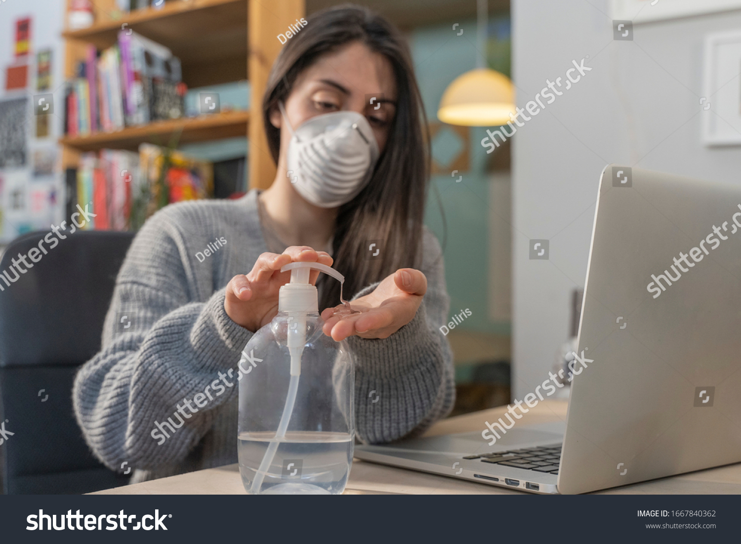 Coronavirus. Business woman working from home wearing protective mask. Business woman in quarantine for coronavirus wearing protective mask. Working from home.  Cleaning her hands with sanitizer gel.  #1667840362