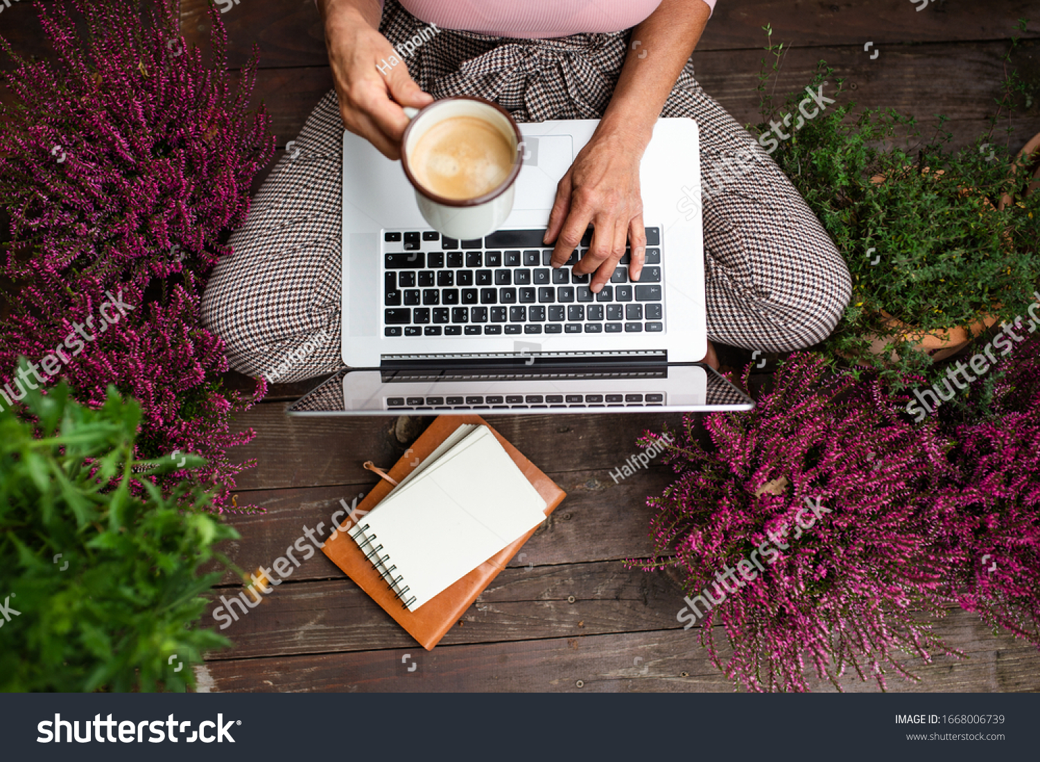 Top view of senior woman with laptop sitting outdoors on terrace, working.