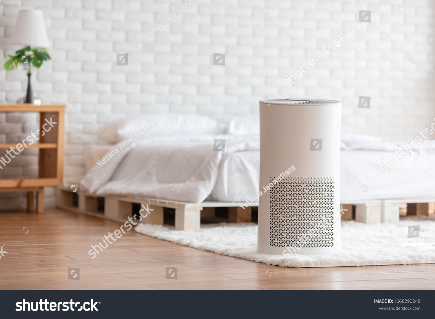 Air purifier in cozy white bedroom for filter and cleaning removing dust PM2.5 HEPA in home,for fresh air and healthy life,Air Pollution Concept #1668290248