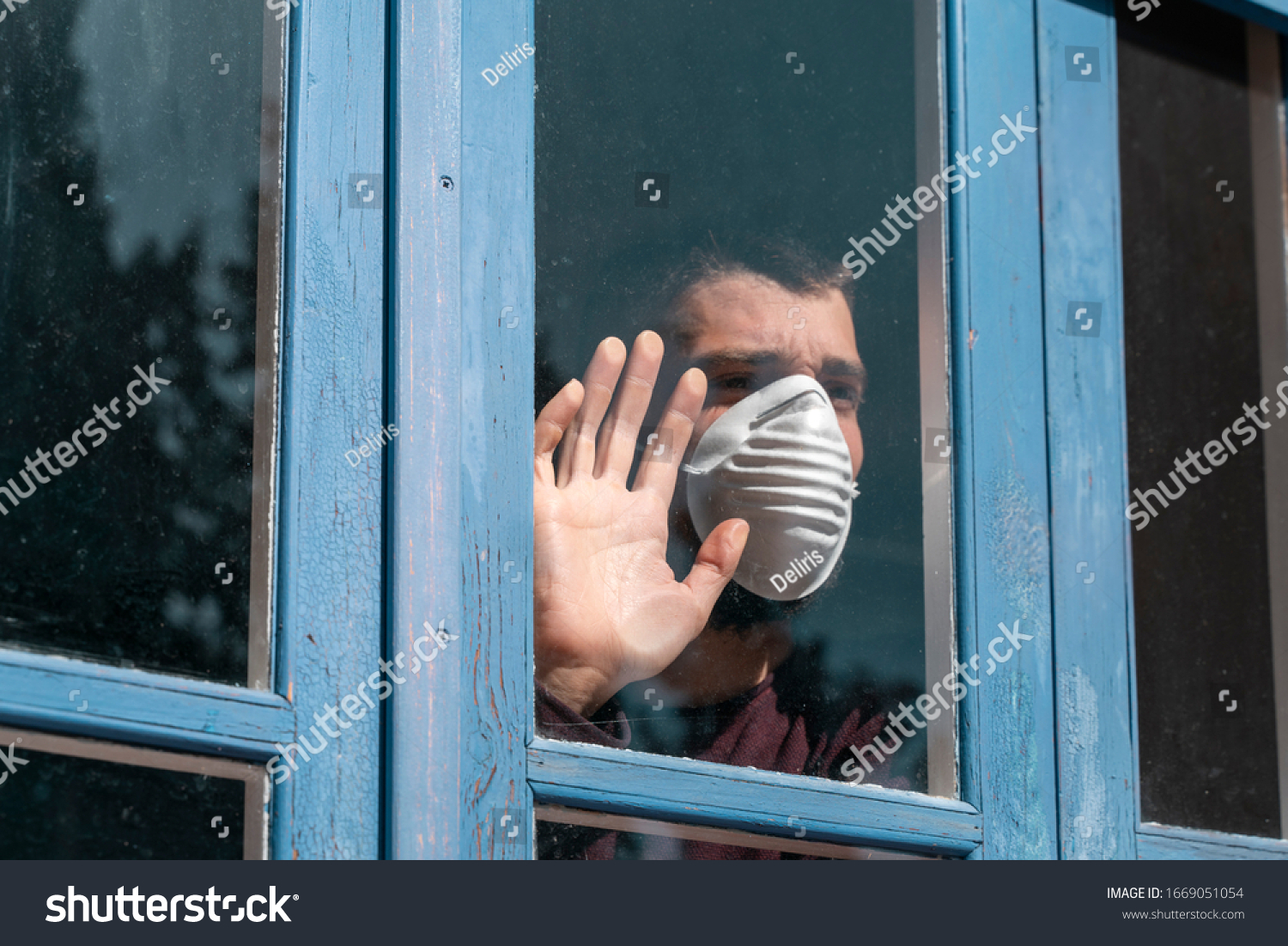 Coronavirus. Sick man of corona virus  looking through the window and wearing mask protection and recovery from the illness in home. Quarantine. Patient isolated to prevent infection. Pandemia. House. #1669051054