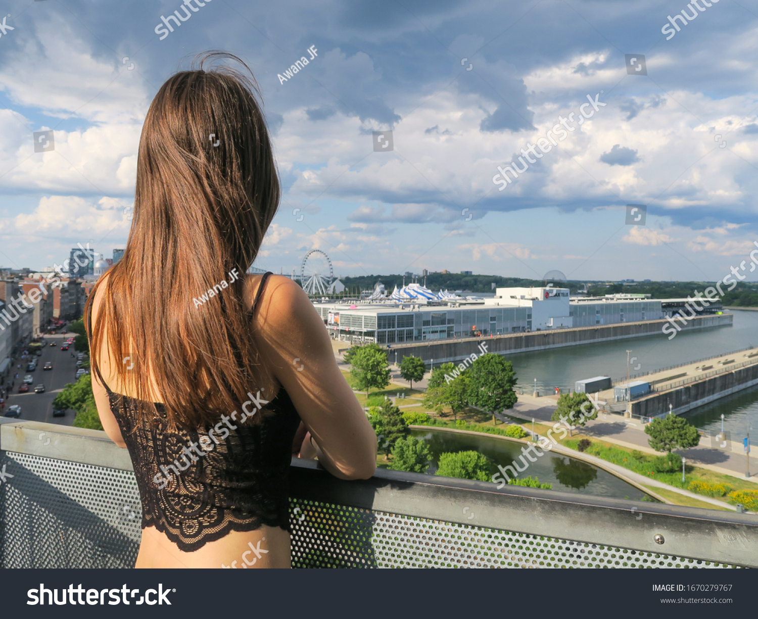 Montreal, Canada - july 2019 : back view of a young woman looking towards the port of Montreal, at the Pointe-à-Callière Museum belvedere