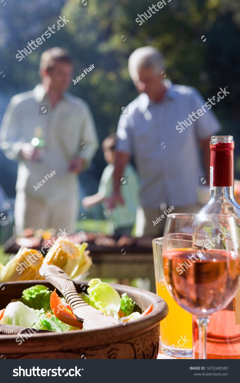 Men cooking food at family barbeque in garden with wine on table #1670340580