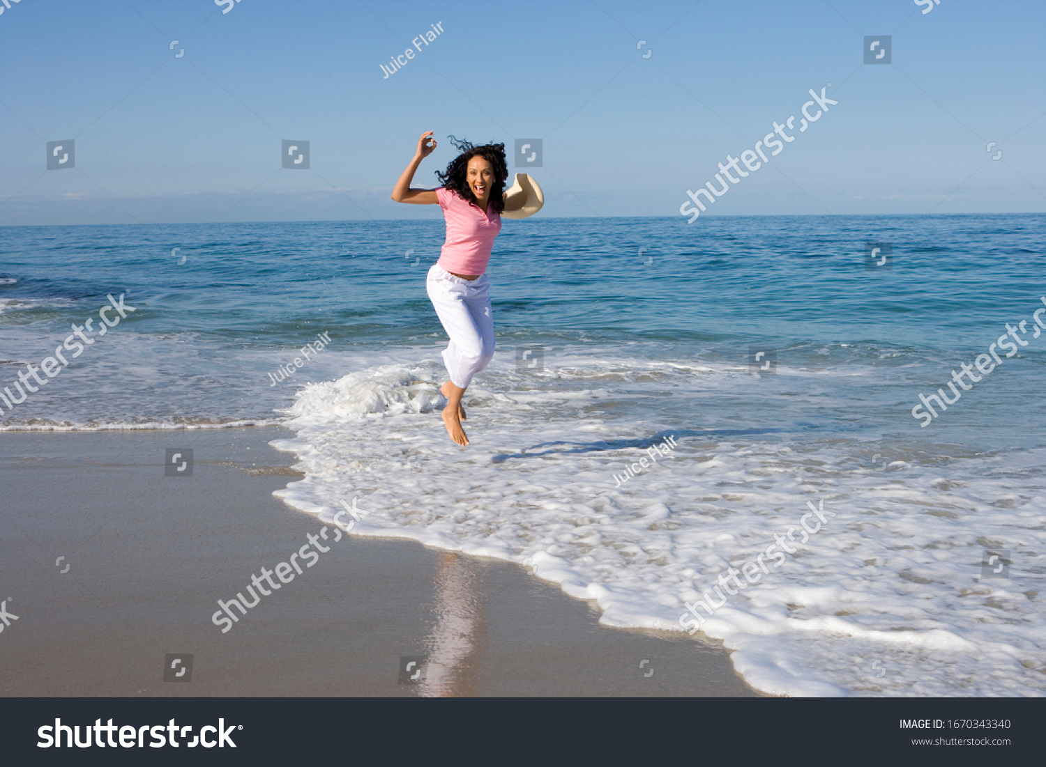 Woman jumping in waves on beach on summer vacation at camera #1670343340
