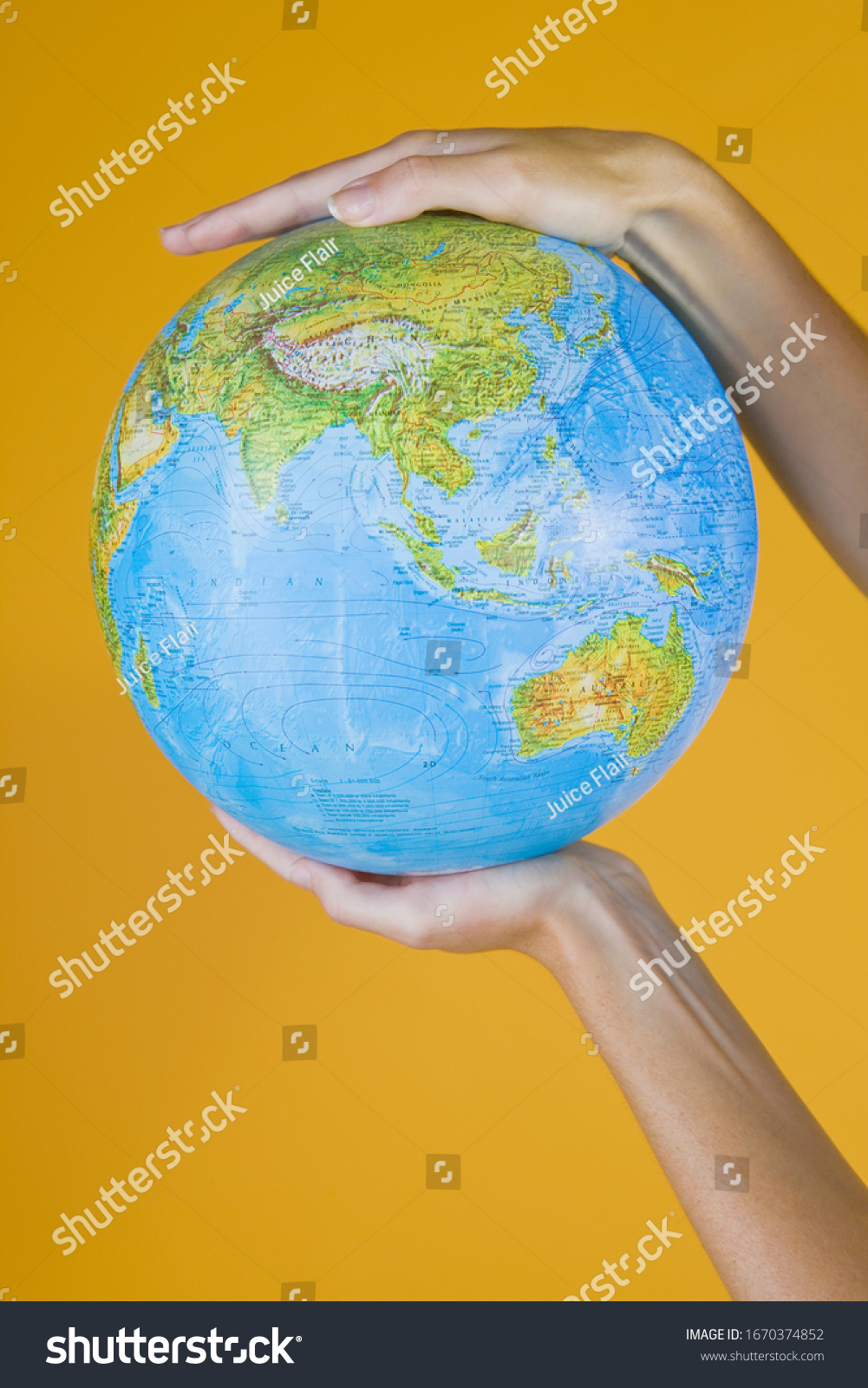 Studio concept with hands holding globe against yellow background #1670374852