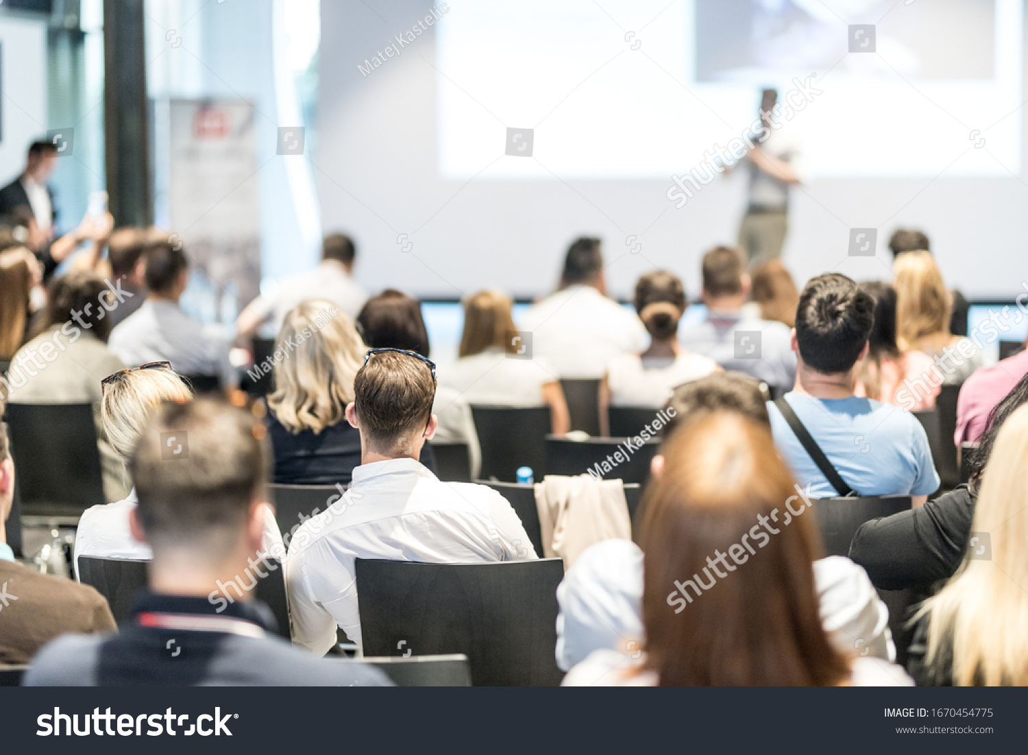 Business and entrepreneurship symposium. Speaker giving a talk at business meeting. Audience in conference hall. Rear view of unrecognized participant in audience. #1670454775