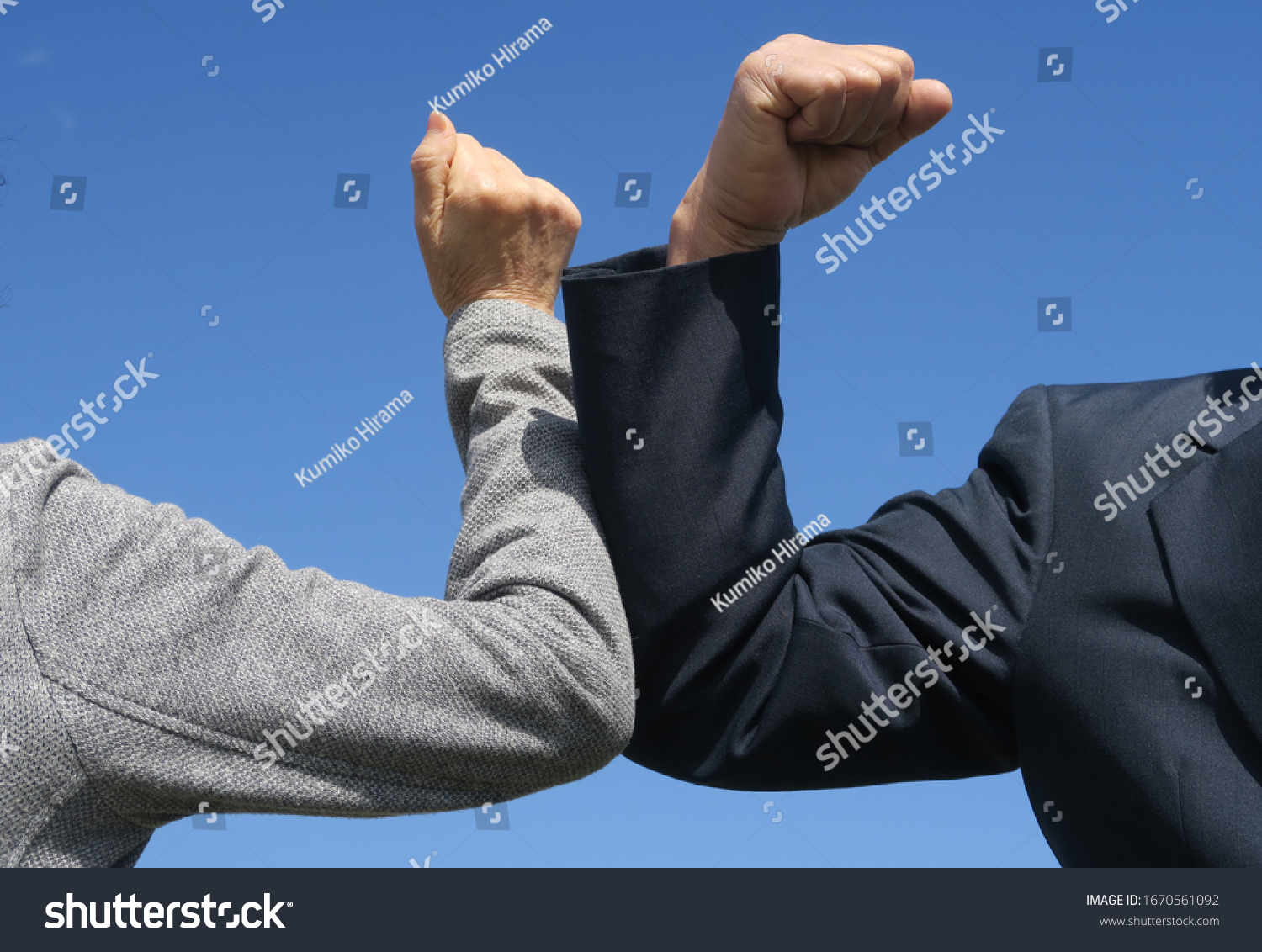 Elbow bumping. A new way of greeting to avoid the spread of coronavirus (COVID-19). Two people (a man and a woman) bump elbows instead of hug or handshake. New normal. #1670561092