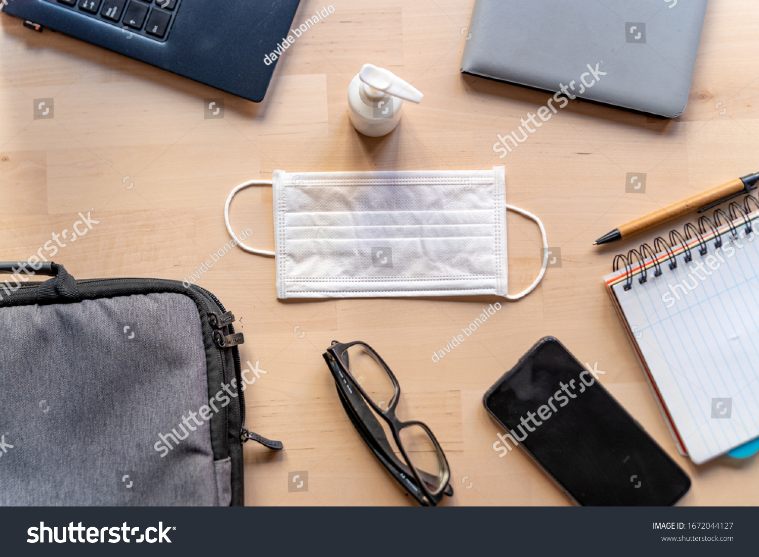 remote work kit on wooden office desk with hand sanitizer and face mask, a solution against the spread of corona virus for quarantined employees #1672044127