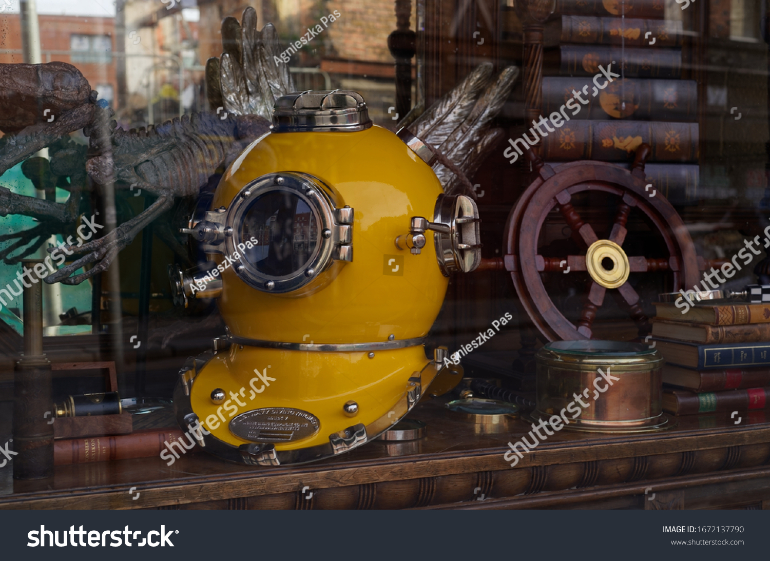 DUBLIN, IRELAND - MARCH 5, 2020: Antique shop window with old yellow shiny diving helmet and other restored items. Vintage collection.