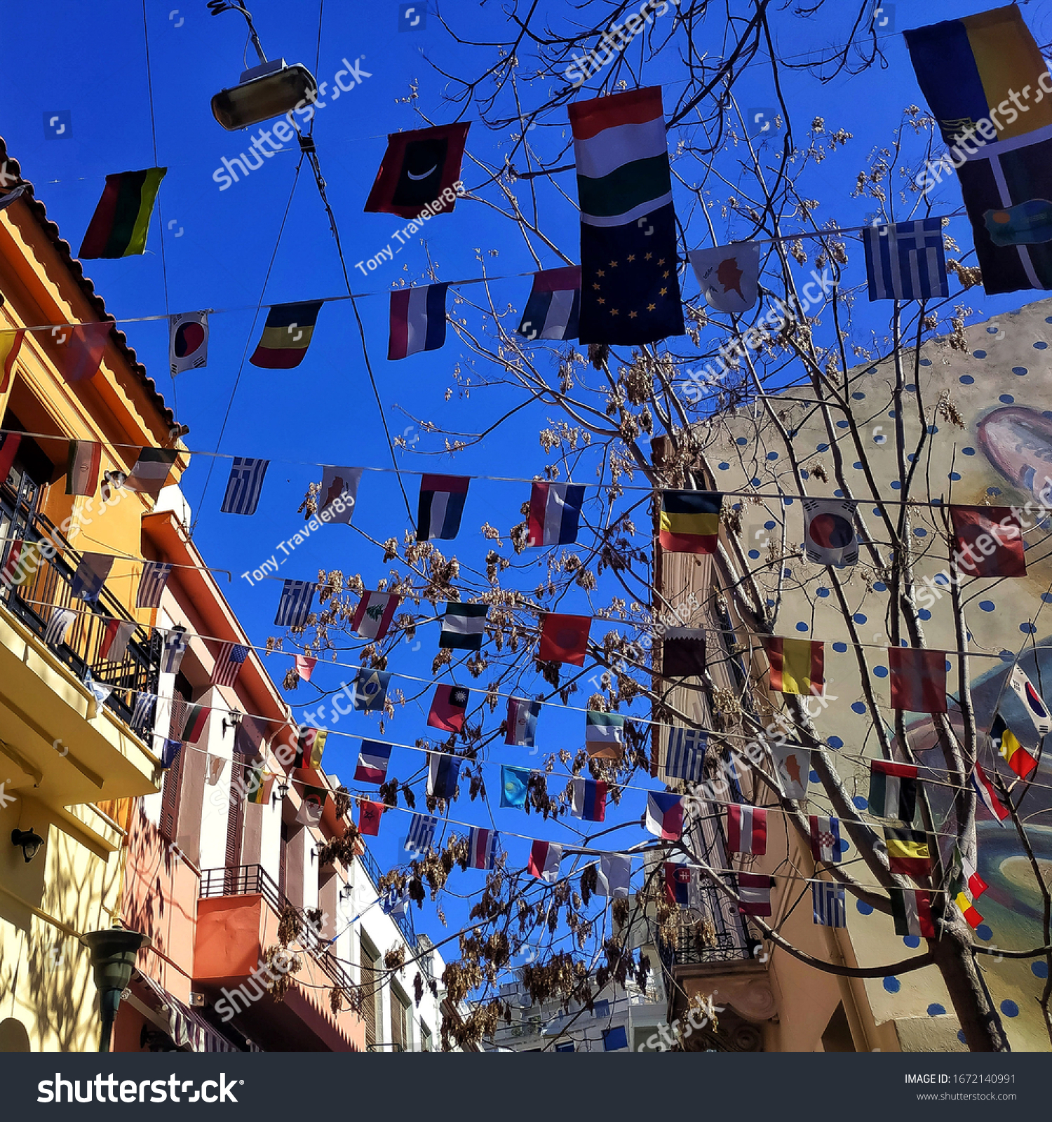 Waving world flags against a blue sky and colorful buildings