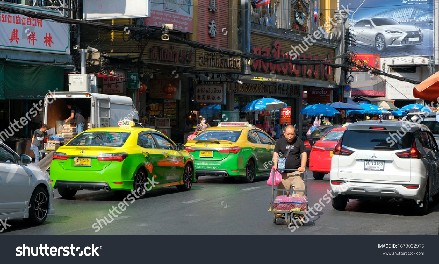 BANGKOK, THAILAND - MARCH 6, 2020: An unidentified man pushes a trolley while crossing a street amidst traffic on March 6, 2020 in Thai capital Bangkok