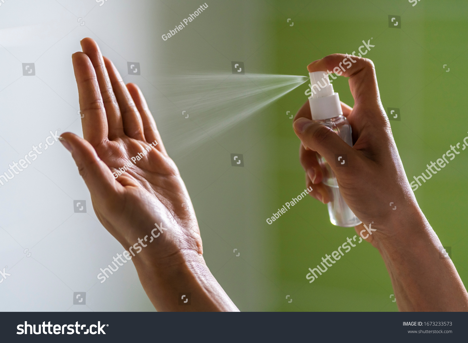 Caucasian woman wipes her hands with an alcohol-based hand-washing spray as a preventive hygiene measure against coronavirus ( Sars-CoV-2, Covid-19) infection. Antibacterial hand sanitizer gel. #1673233573