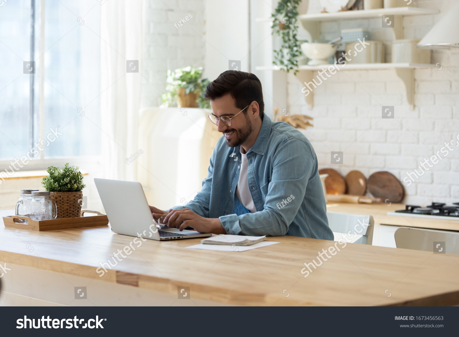 Smiling young man working on laptop in modern kitchen, checking email in morning, writing message in social network, happy young male using internet banking service, searching information #1673456563