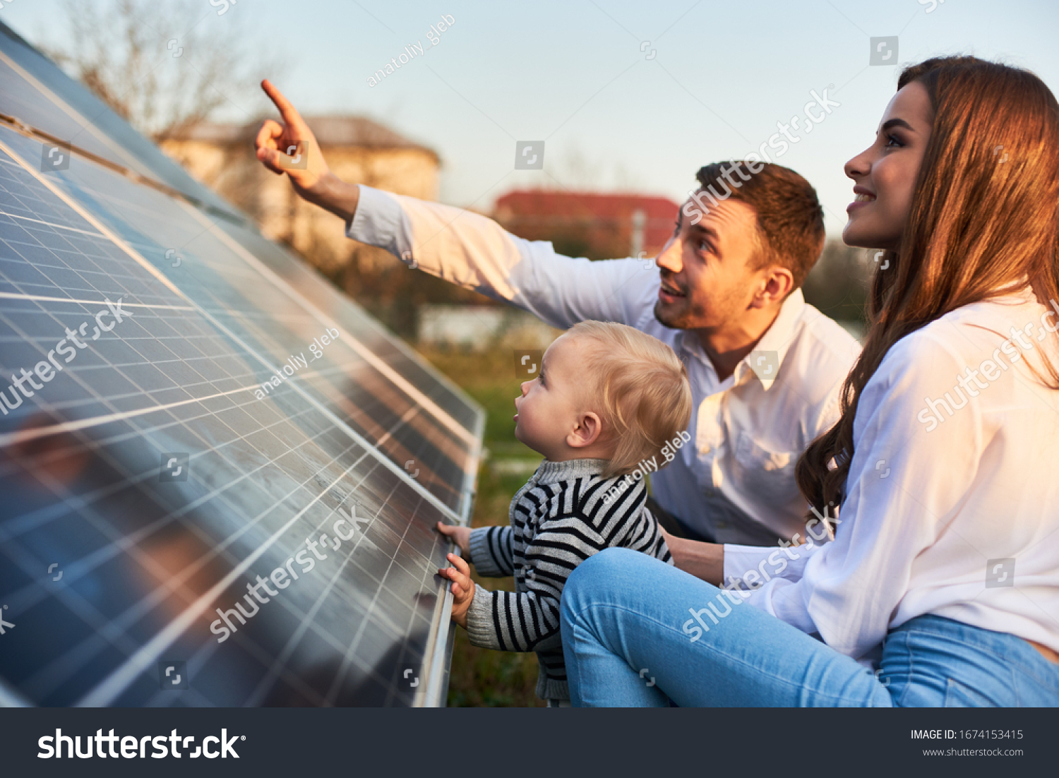 Man shows his family the solar panels on the plot near the house during a warm day. Young woman with a kid and a man in the sun rays look at the solar panels. #1674153415