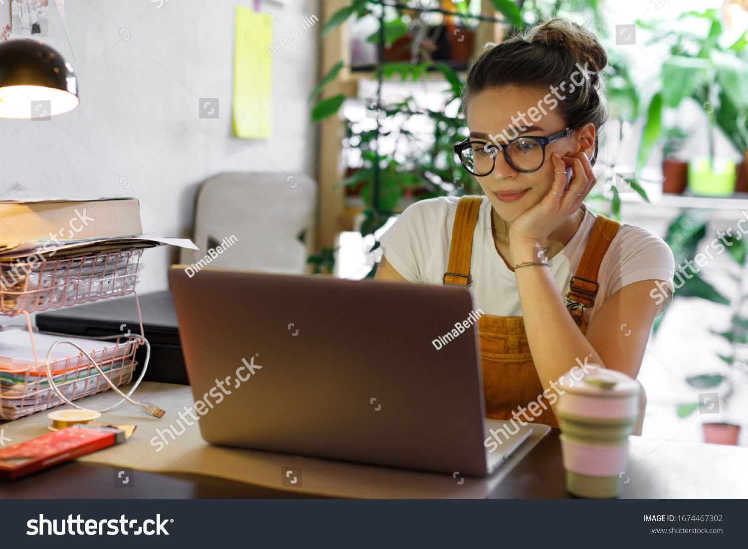 Young female gardener in glasses using laptop, communicates on internet with customer in home garden/greenhouse, reusable coffee/tea mug on table.Cozy office workplace, remote work, E learning concept #1674467302