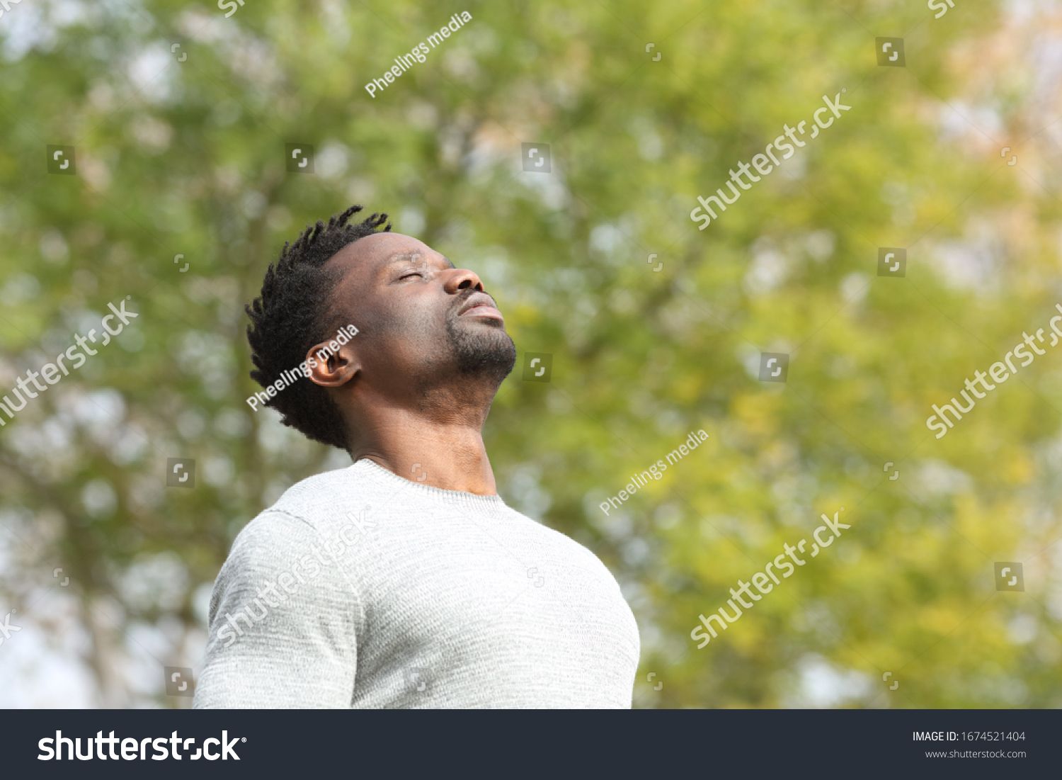 Black serious man breathing deeply fresh air in a park a sunny day with a green tree in the background #1674521404