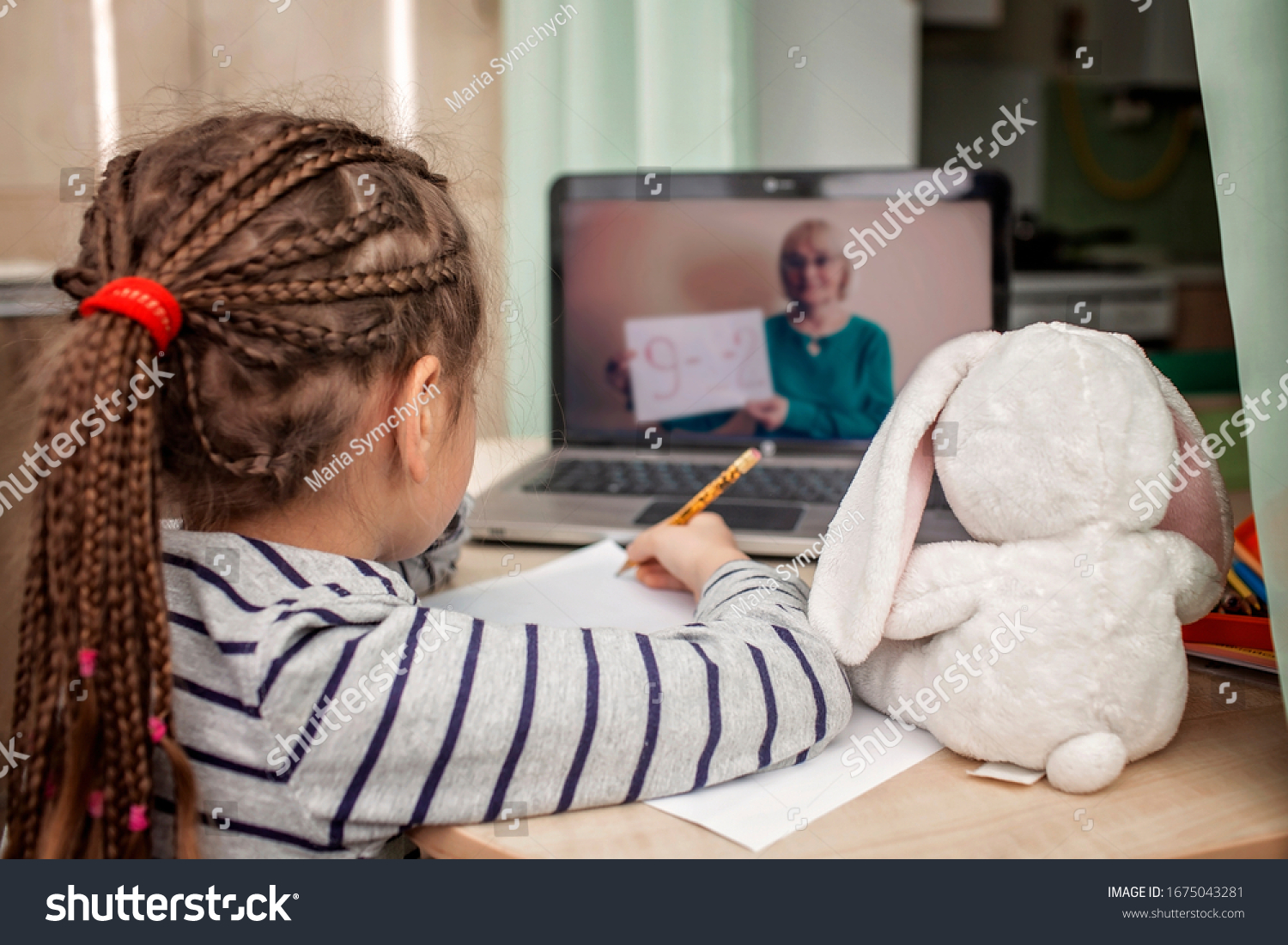 Pretty stylish schoolgirl studying math during her online lesson at home, social distance during quarantine, self-isolation, online education concept #1675043281