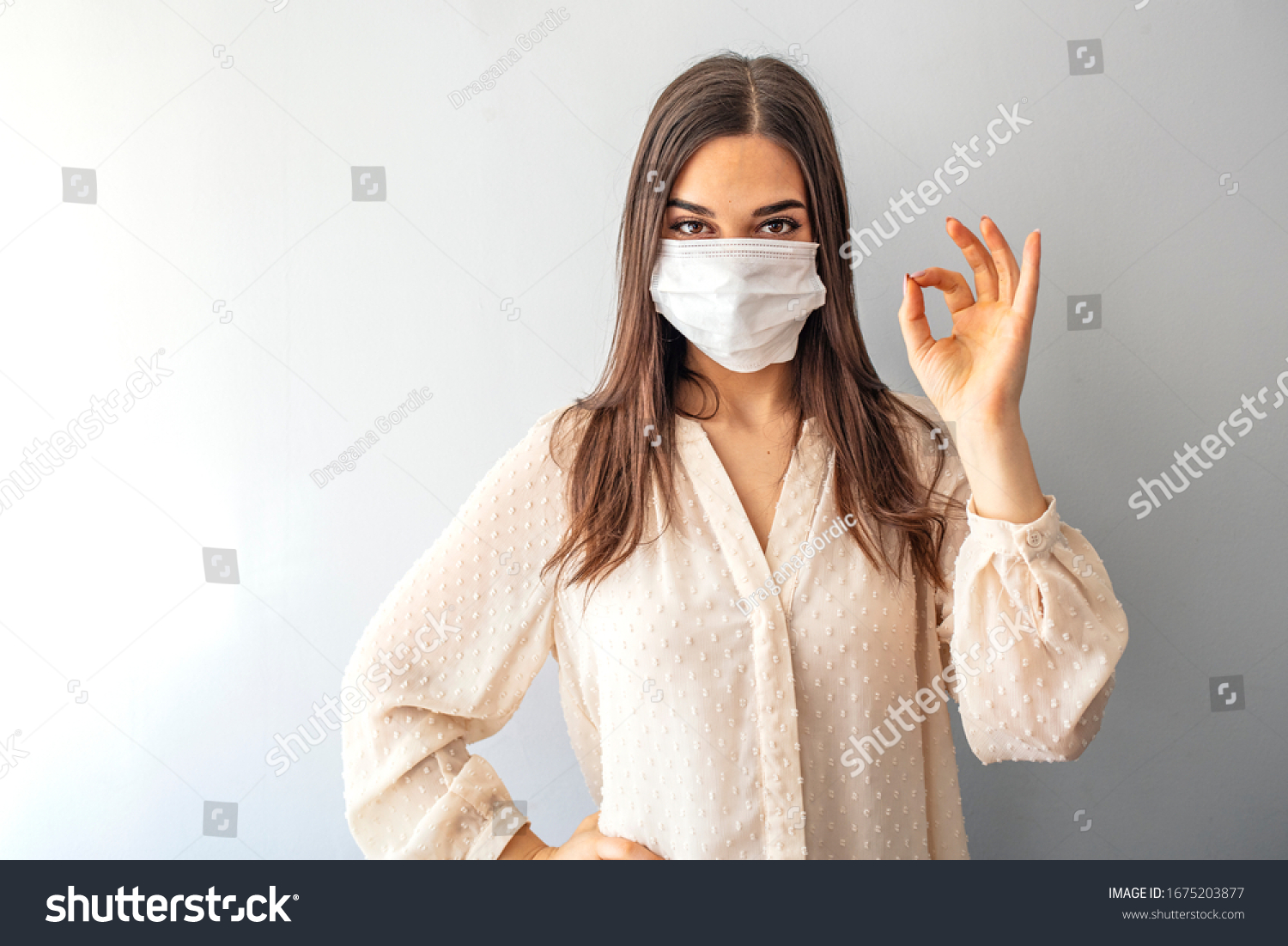 Young woman wearing medical face mask, studio portrait. Woman Wearing Protective Mask and Showing OK sign. Woman wearing surgical mask for corona virus #1675203877