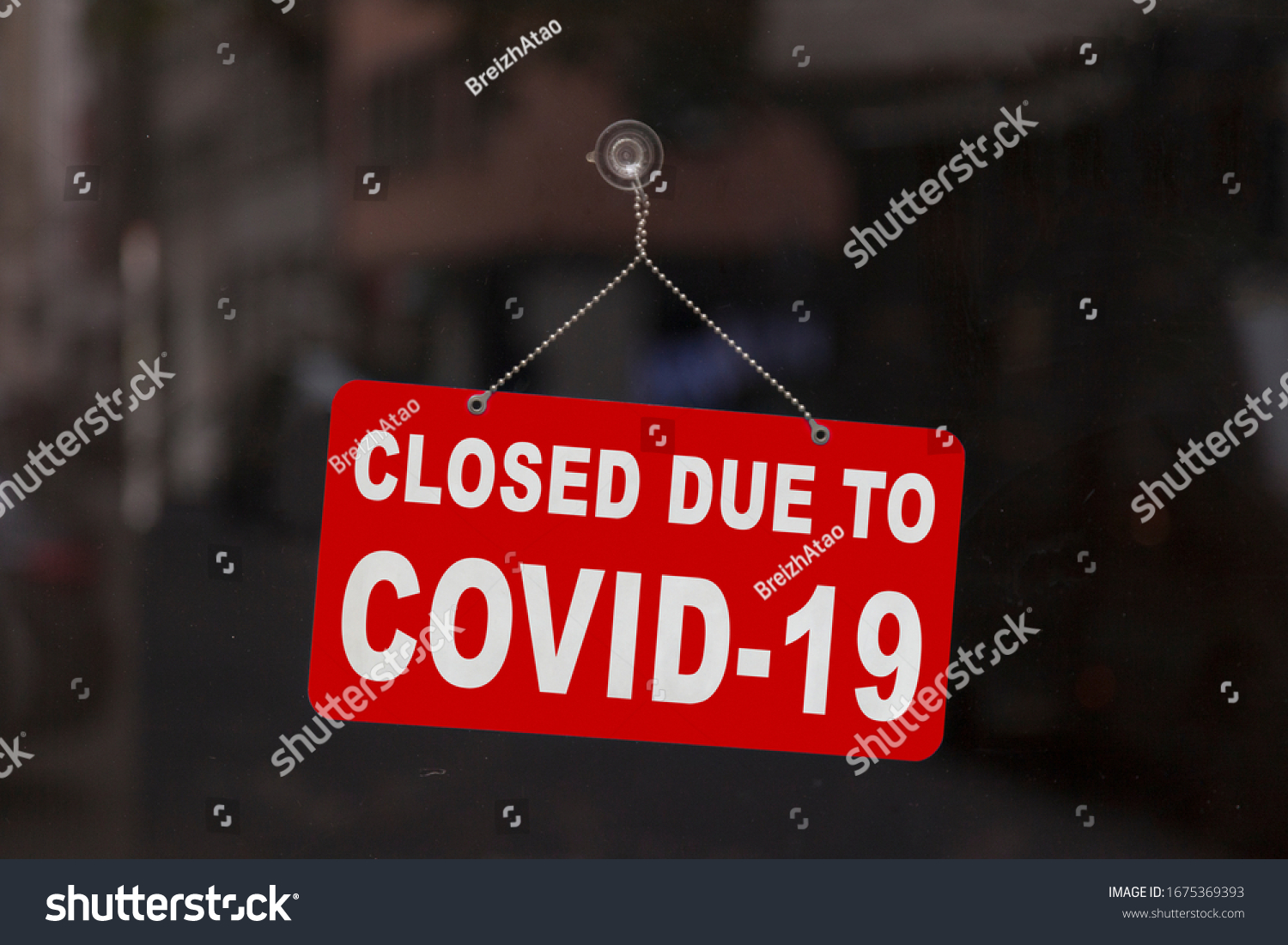 "Close-up on a red closed sign in the window of a shop displaying the message ""Closed due to Covid-19"". #1675369393"