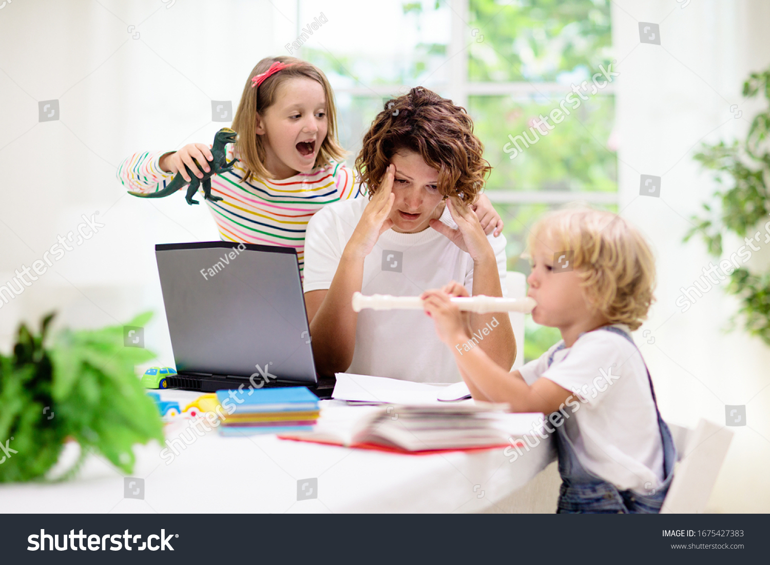 Mother working from home with kids. Quarantine and closed school during coronavirus outbreak. Children make noise and disturb woman at work. Homeschooling and freelance job. Boy and girl playing. #1675427383
