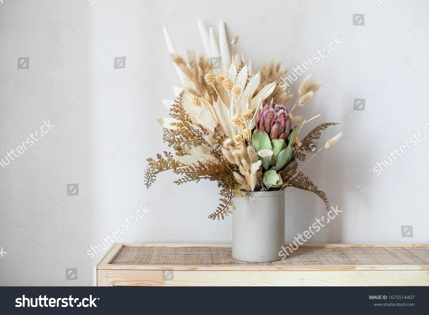 Minimalistic composition of dried flowers in cylindrical ceramic vase as home decoration.  #1675514407