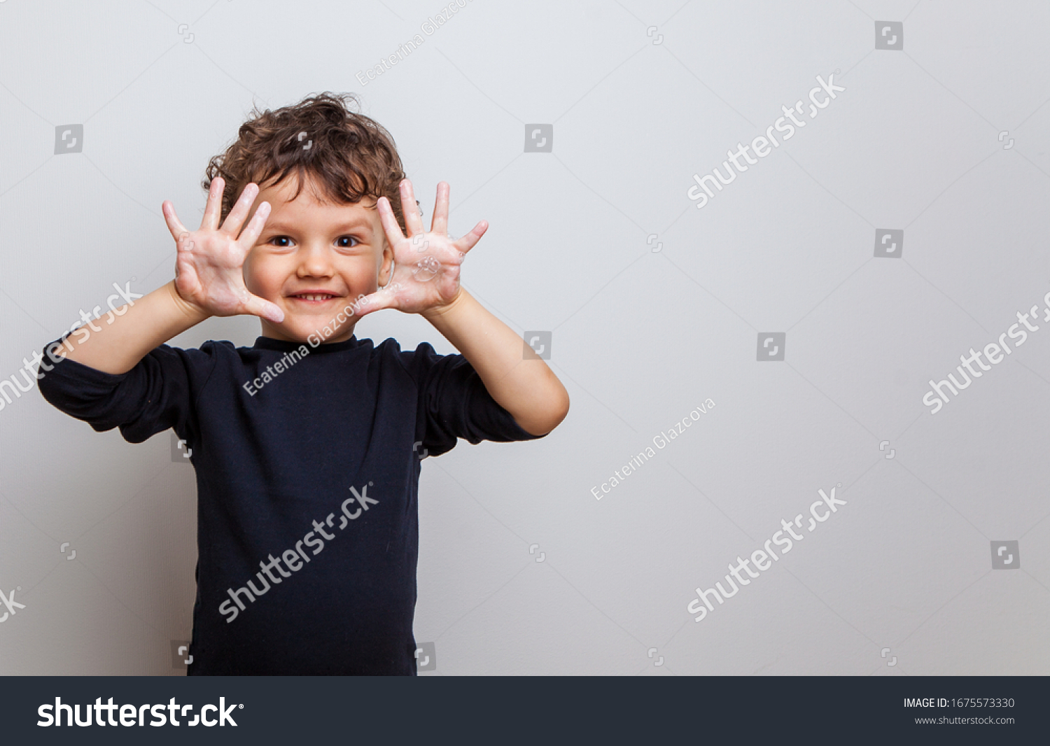 cute baby shows soaped hands to the camera. hygiene procedures. prevention of viral and bacterial diseases. Hand disinfection. studio photo isolated on white background #1675573330
