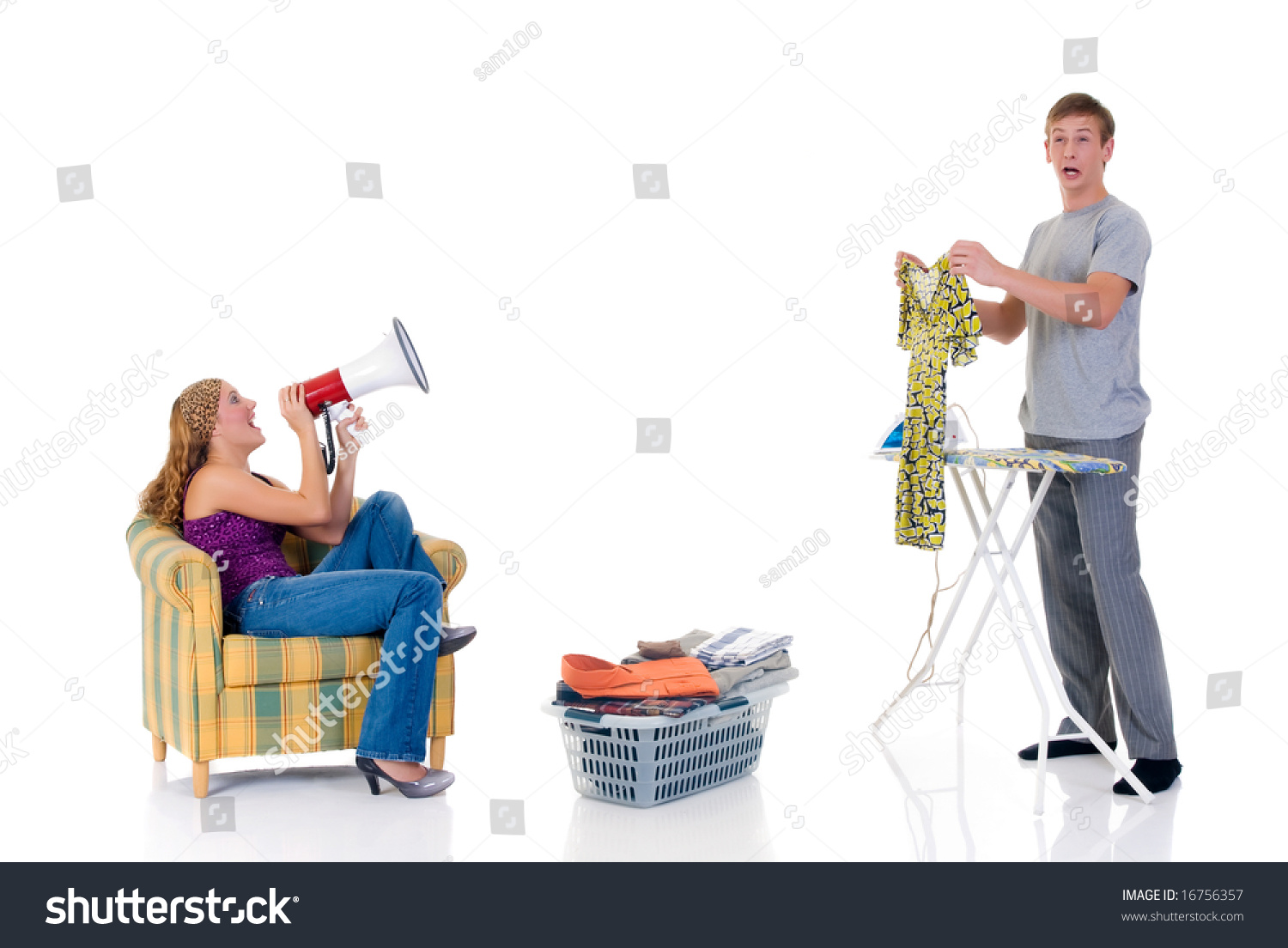 0d1e4bb96a Young bossy woman shouting with megaphone to husband ironing clothing.  Studio