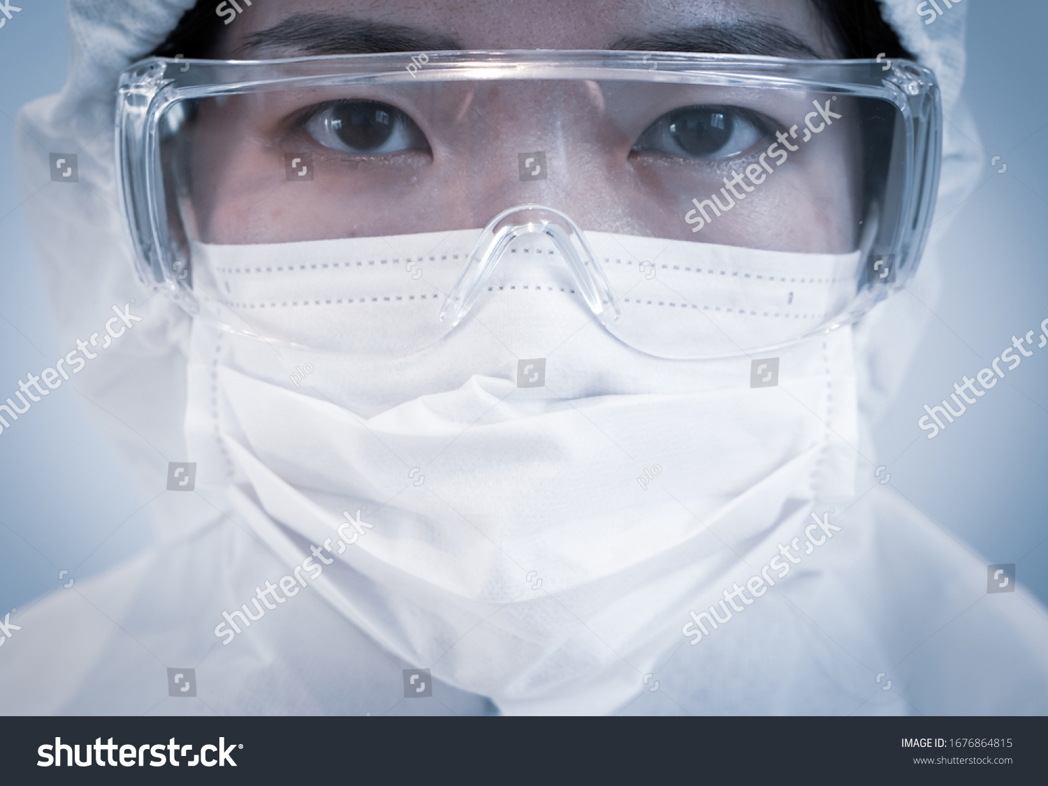 A doctor wearing personal protective equipment or ppe including mask, goggle, and suit to protect COVID-19 infection. coronavirus, medical, healthcare, quarantine concept #1676864815